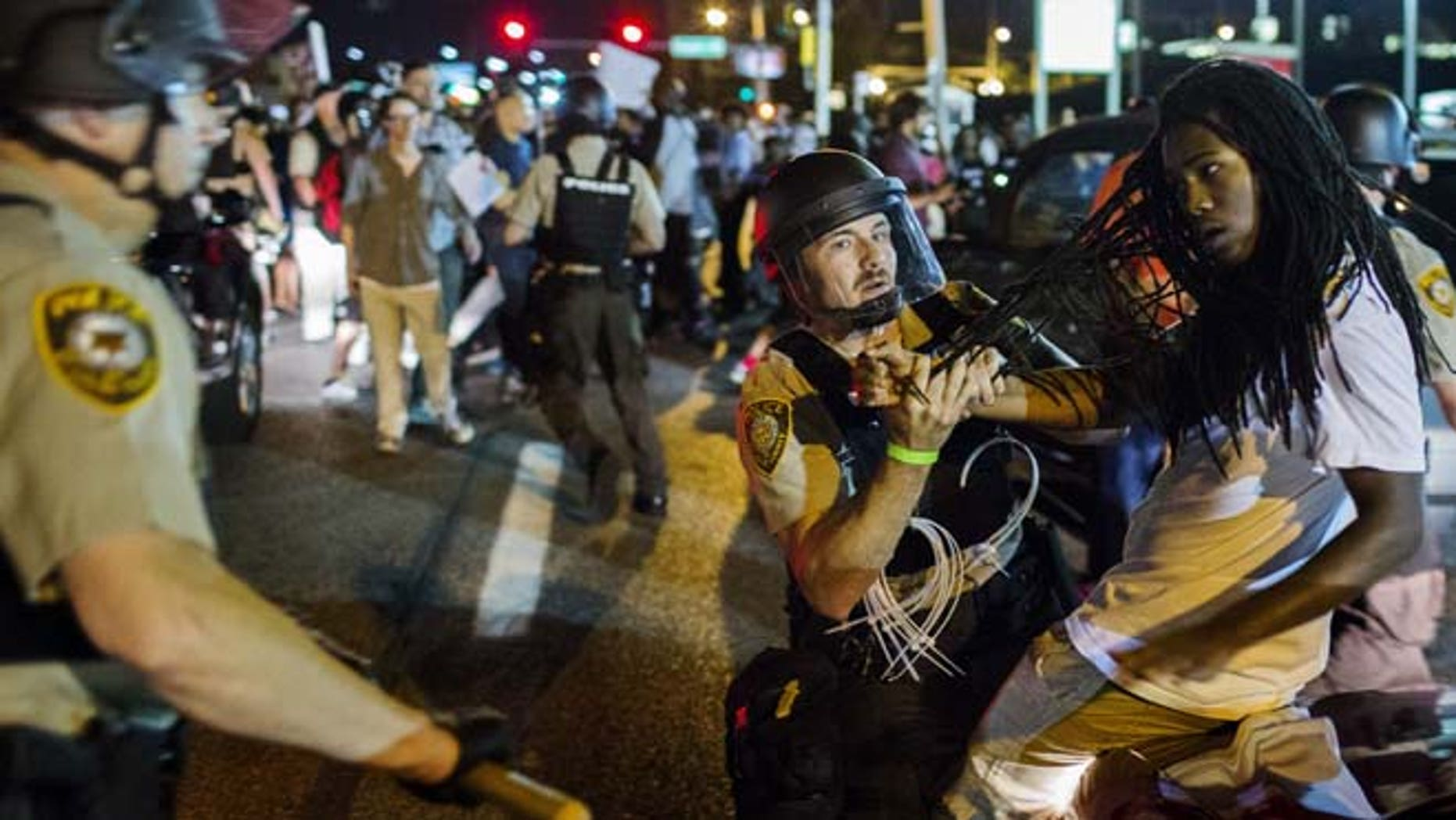 Aug. 10, 2015: St Louis County police officers hold an anti-police demonstrator in Ferguson, Missouri.