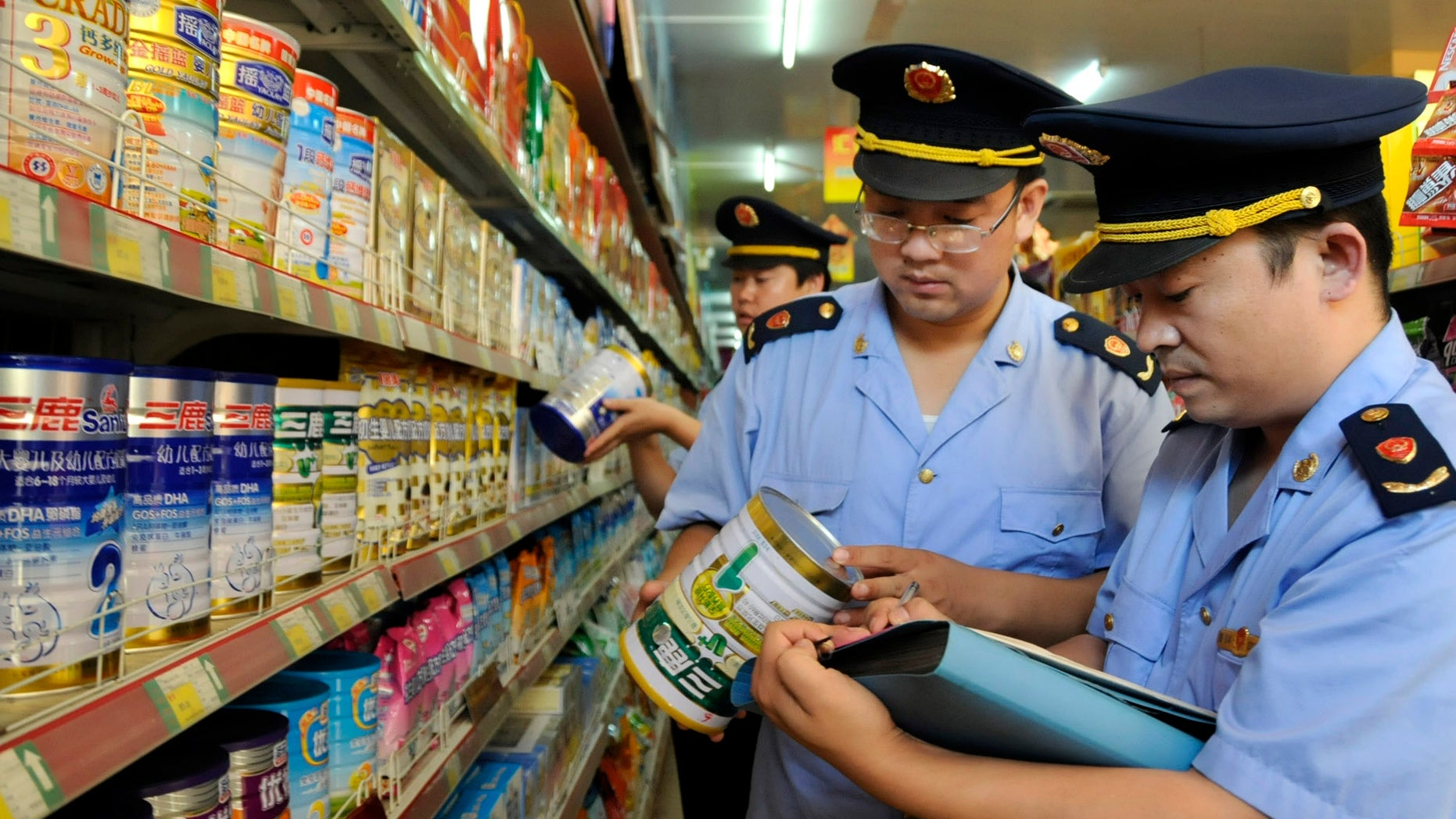 Local industry and commerce administrative bureau personnel check Sanlu formula milk products at a supermarket in Zaozhuang, Shandong province, September 12, 2008. China's Health Ministry has launched a nationwide investigation into the infant kidney stone case related with domestic milk powder, Sanlu formula, and asked all local health agencies to report relevant cases immediately, Xinhua News Agency reported. REUTERS/China Daily (CHINA).  CHINA OUT. NO COMMERCIAL OR EDITORIAL SALES IN CHINA. - RTX8P0V