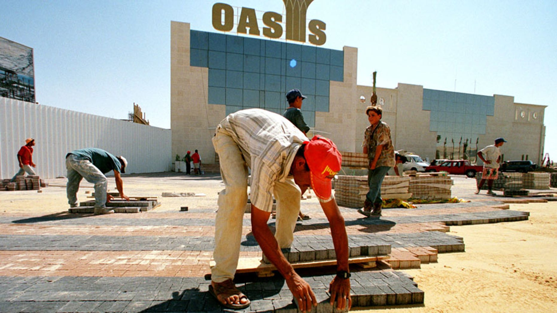 Palestinian laborers lay colored bricks in sand September 14, 1998 as they finish the entrance to the Oasis Casino.
