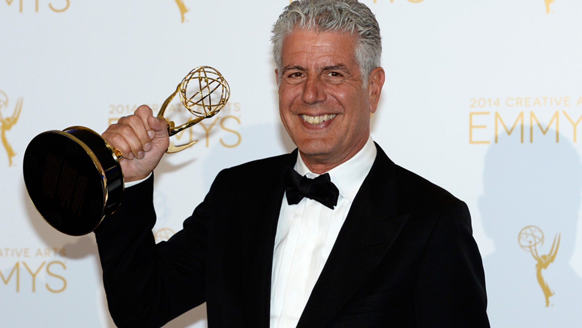 """Anthony Bourdain poses backstage with the Emmy for Outstanding Informational Series """"Anthony Bourdain: Parts Unknown"""" at the 2014 Creative Arts Emmy Awards in Los Angeles."""