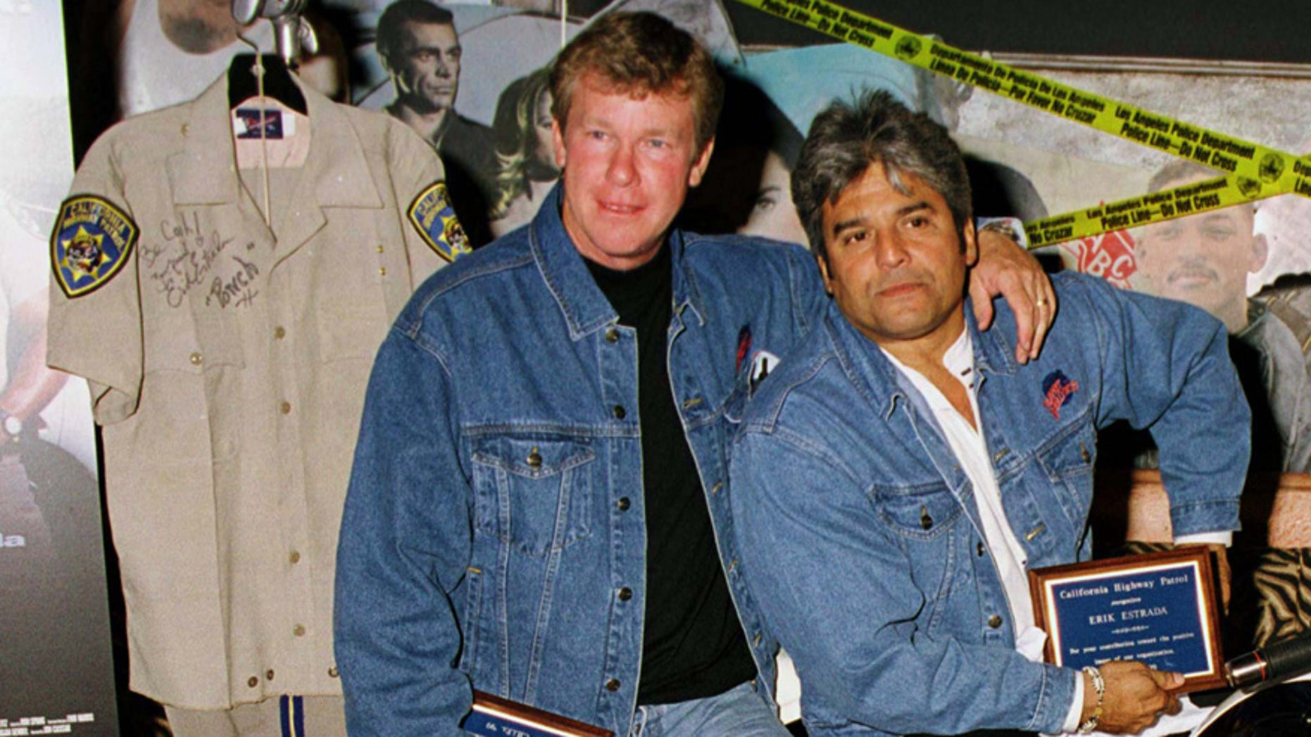 """Actors Larry Wilcox (L) and Erik Estrada, stars of the original television series """"CHiPs"""" pose with a uniform they donated to the memorabilia collection at Planet Hollywood Beverly Hills."""