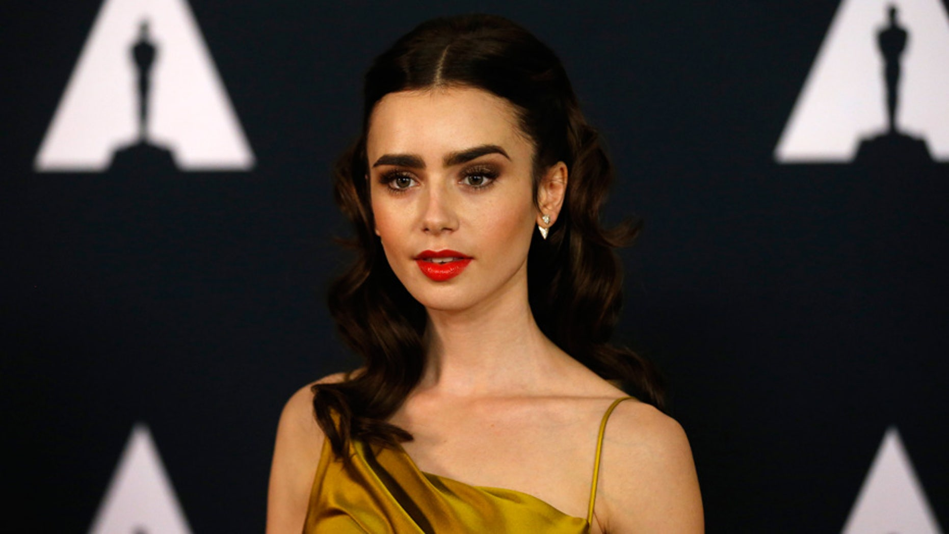 Lily Collins poses at an event.