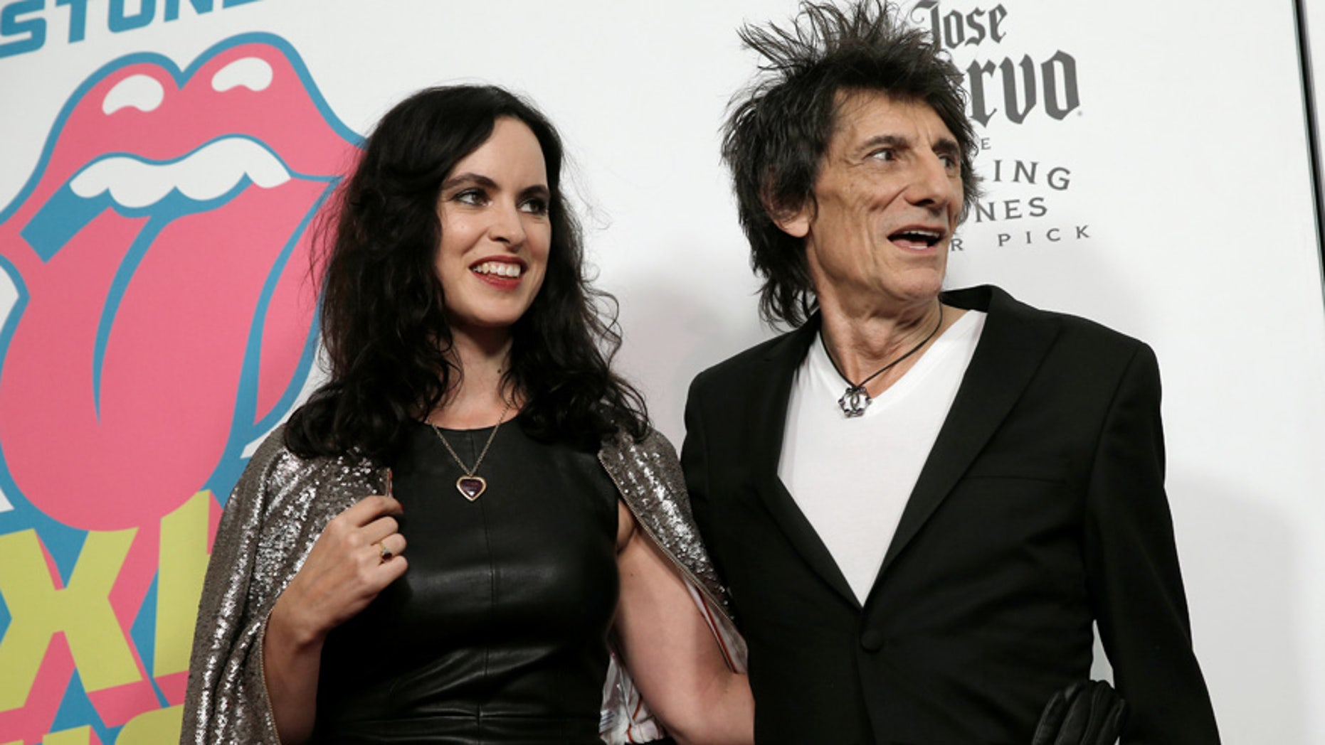 """Rolling Stones member Ronnie Wood and his wife Sally Humphreys pose for photographers at the opening of the new exhibit """"Exhibitionism: The Rolling Stones"""" in New York City on November 15, 2016."""