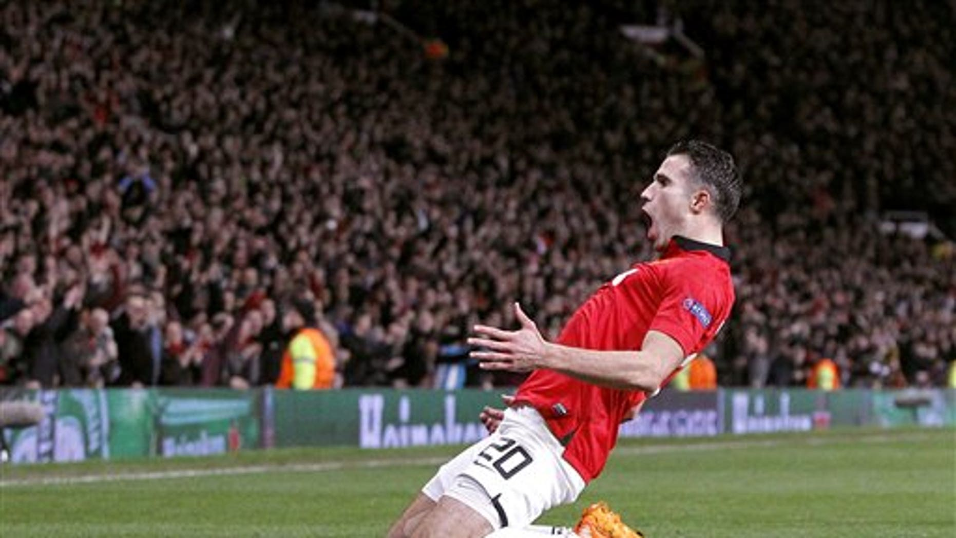 Manchester United's Robin van Persie celebrates scoring his side's third goal  and his hat-trick, during the Champions League, Round of 16, second leg match against Olympiakos,  at Old Trafford, Manchester,  England, Wednesday March 19, 2014. (AP Photo /PA, Peter Byrne) UNITED KINGDOM OUT NO SALES NO ARCHIVE