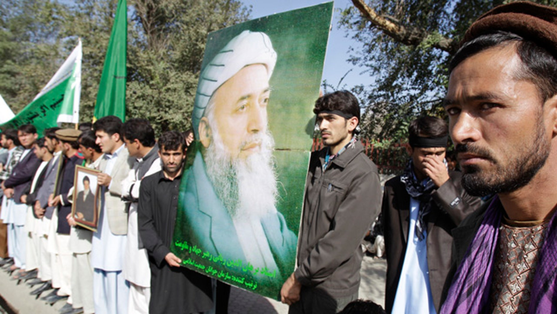 Sept. 21: A  man holds a poster of former Afghan President Burhanuddin Rabbani during a rally  in Kabul, after he was killed by a blast the previous day.