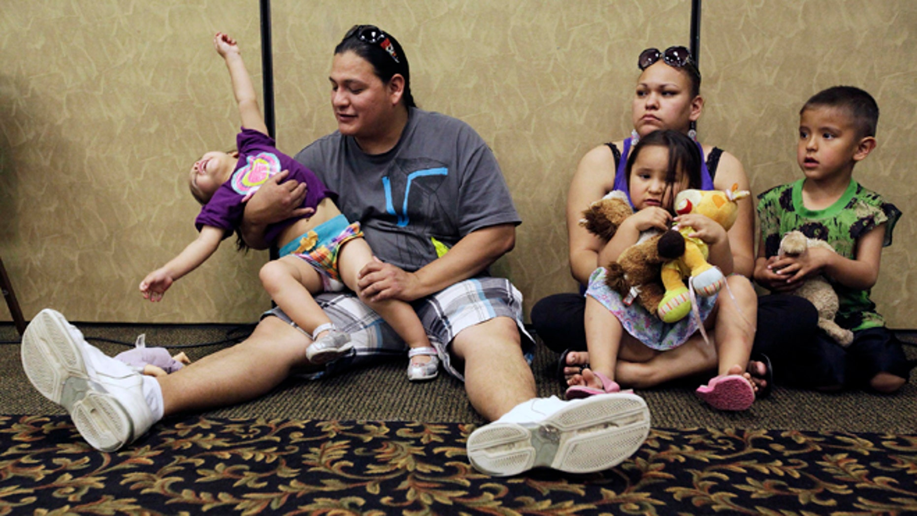 FILE - In this Wednesday, May 15, 2013 file photo, Elijah Bearsheart, left, holds his daughter, Keanala, 1, as he sits with his family, Kehala Diserly, Kiari Diserly, 3, and Yamni Pederson, 5, as they listen to testimony during the Indian Child Welfare Act summit in Rapid City, S.D. A new report on child well-being, measured by state and race, has turned an unflattering spotlight on some places not used to being at the bottom of such lists, including Wisconsin, with a worst-in-the-nation ranking for its black children, and South Dakota, with abysmal results for its American Indian youth. The report was released Tuesday, April 1, 2014 by the Annie E. Casey Foundation. (AP Photo/Rapid City Journal, Benjamin Brayfield)
