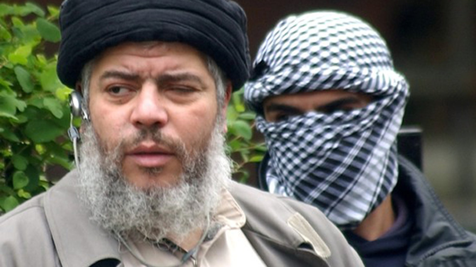 FILE 2004: Abu Hamza al-Masri arrives with a masked bodyguard to conduct prayers in the street outside the closed Finsbury Park Mosque in London