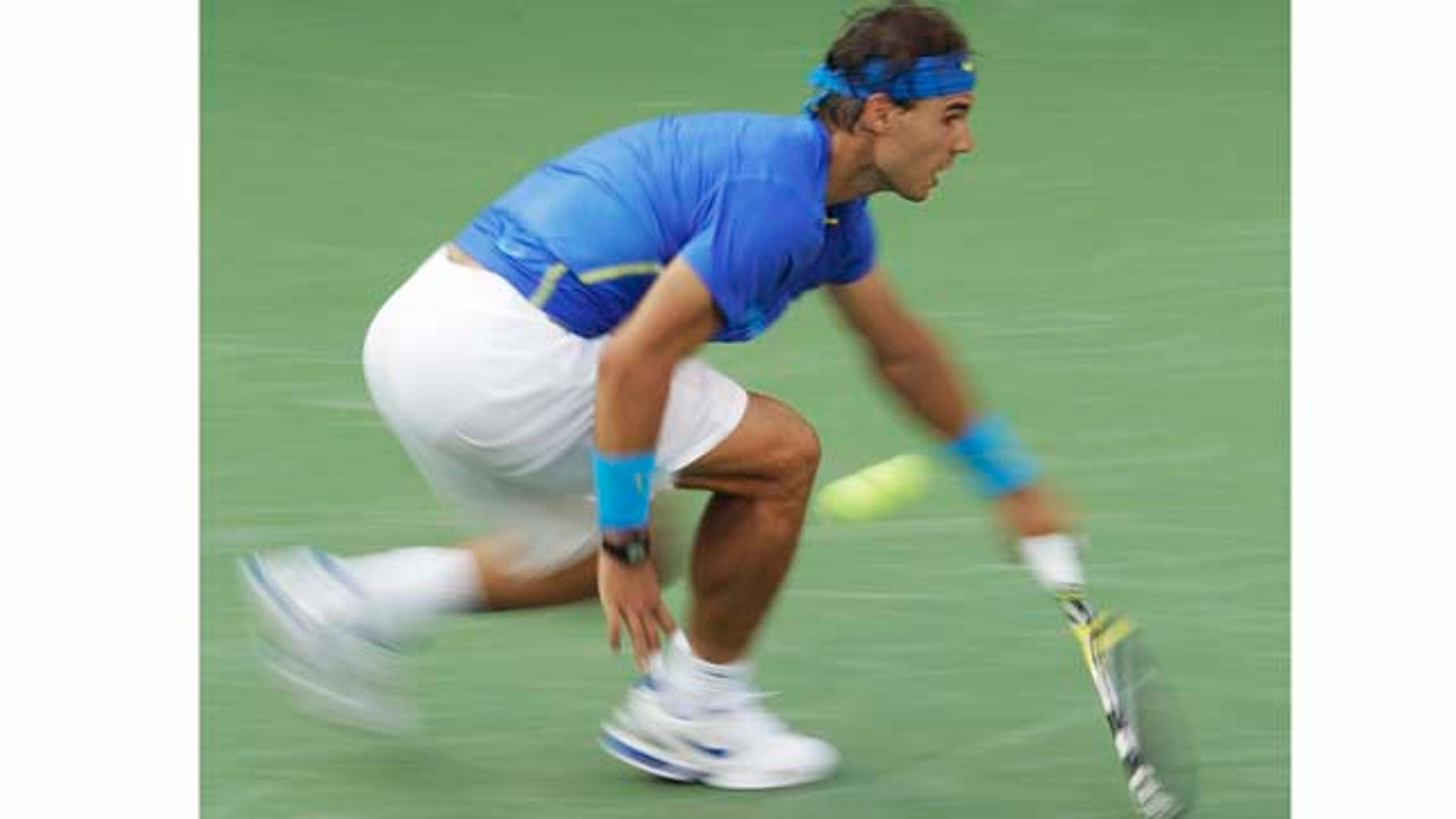 In a photo made using a slow shutter speed to create a blurred effect, Rafael Nadal of Spain returns a shot to Novak Djokovic of Serbia at the U.S. Open tennis tournament in New York, Monday, Sept. 12, 2011. (AP Photo/Charlie Riedel)