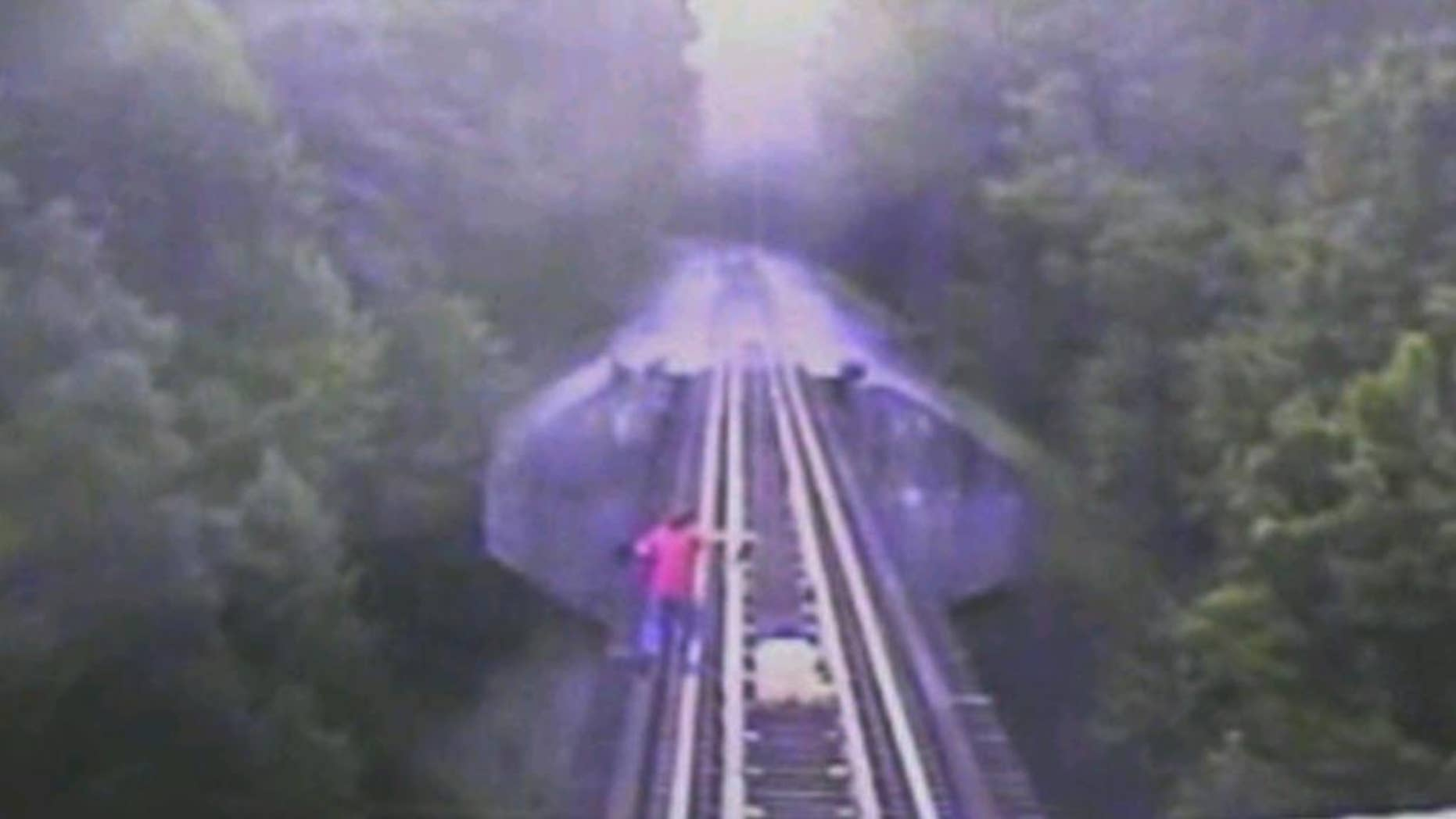 In this frame grab from surveillance video provided by the Indiana Rail Road via WRTV, two women run down a railroad track ahead of a freight train coming toward them, Thursday, July 10, 2014, in Monroe County in Indiana. The women survived the incident, but authorities are reviewing the video for potential criminal charges. (AP Photo/Indiana Rail Road via WRTV)