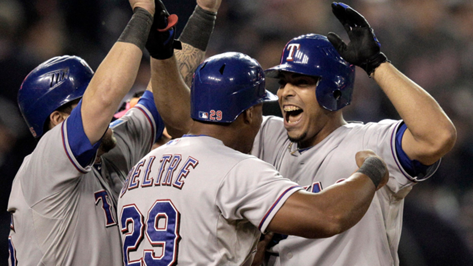 Texas Rangers' Adrian Beltre and Mike Napoli celebrate with teammate Nelson Cruz after his 3-run home run in the 11th inning in Game 4 of baseball's American League championship series against the Detroit Tigers, Wednesday, Oct. 12, 2011, in Detroit. (AP Photo/Charlie Riedel)