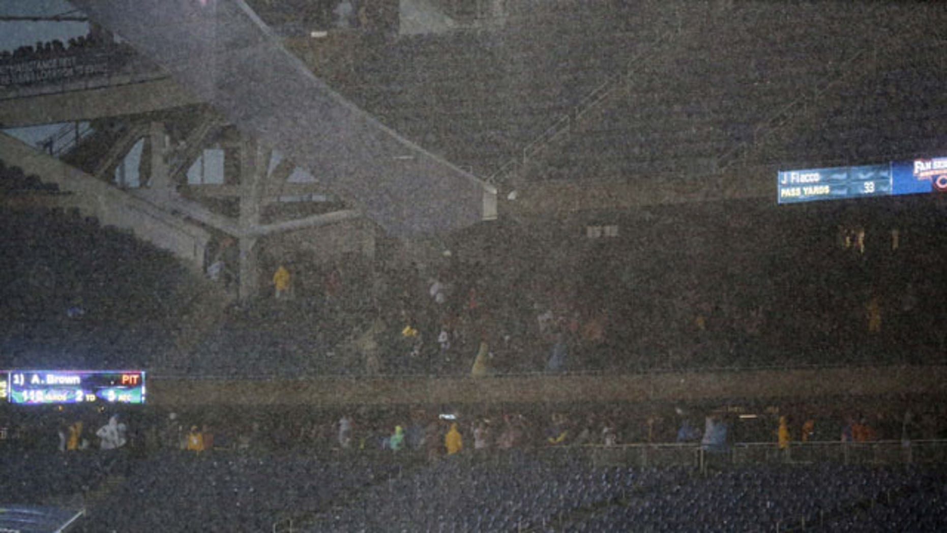 November 17, 2013: Fan seek shelter under the stands as a severe storm blows over Soldier Field in Chicago during the first half of an NFL football game between the Chicago Bears and Baltimore Ravens. (AP Photo)