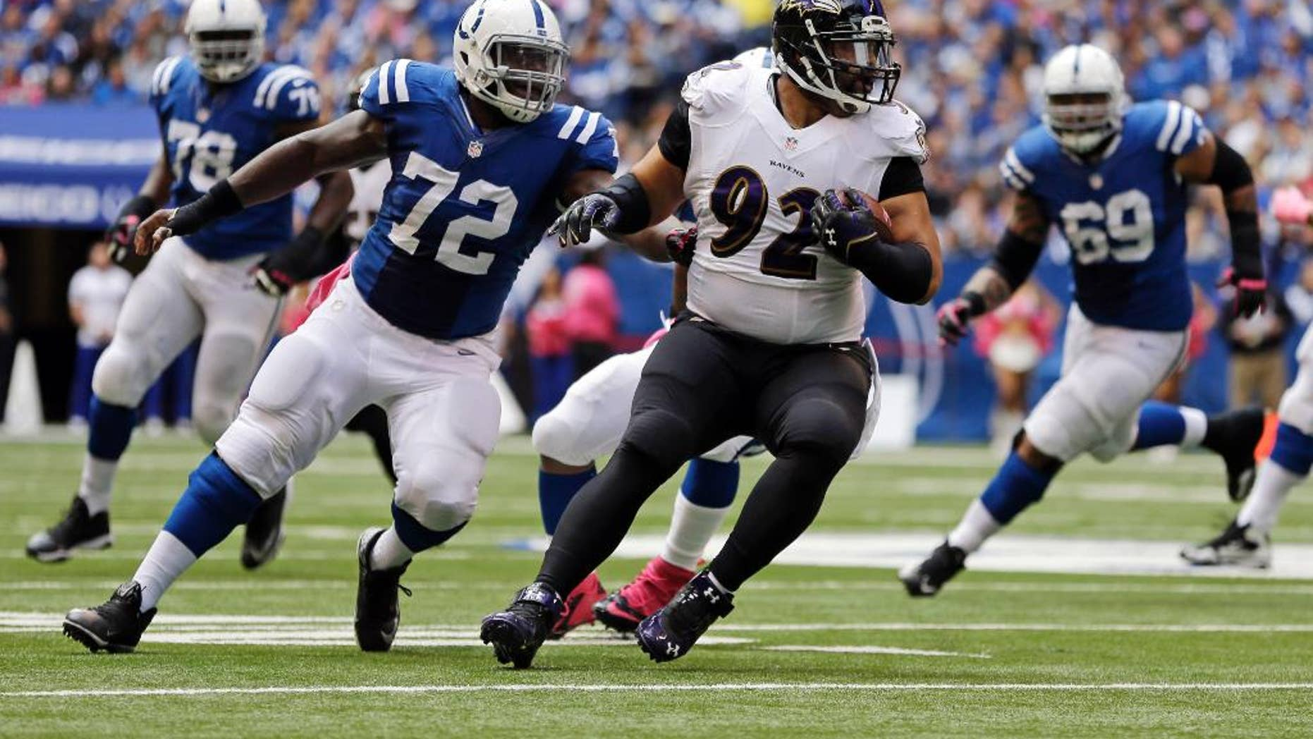 FILE - In this Oct. 5, 2014, file photo, Baltimore Ravens nose tackle Haloti Ngata (92)  is chased by Indianapolis Colts center Jonotthan Harrison (72) after intercepting a pass during the first half of an NFL football game in Indianapolis. There is seemingly no limit to the ways in which Ngata can help the Ravens win. He stops the run, intercepts passes, has served as a blocking back and last Sunday took over as the long snapper for injured Morgan Cox. (AP Photo/Jeff Roberson, File)