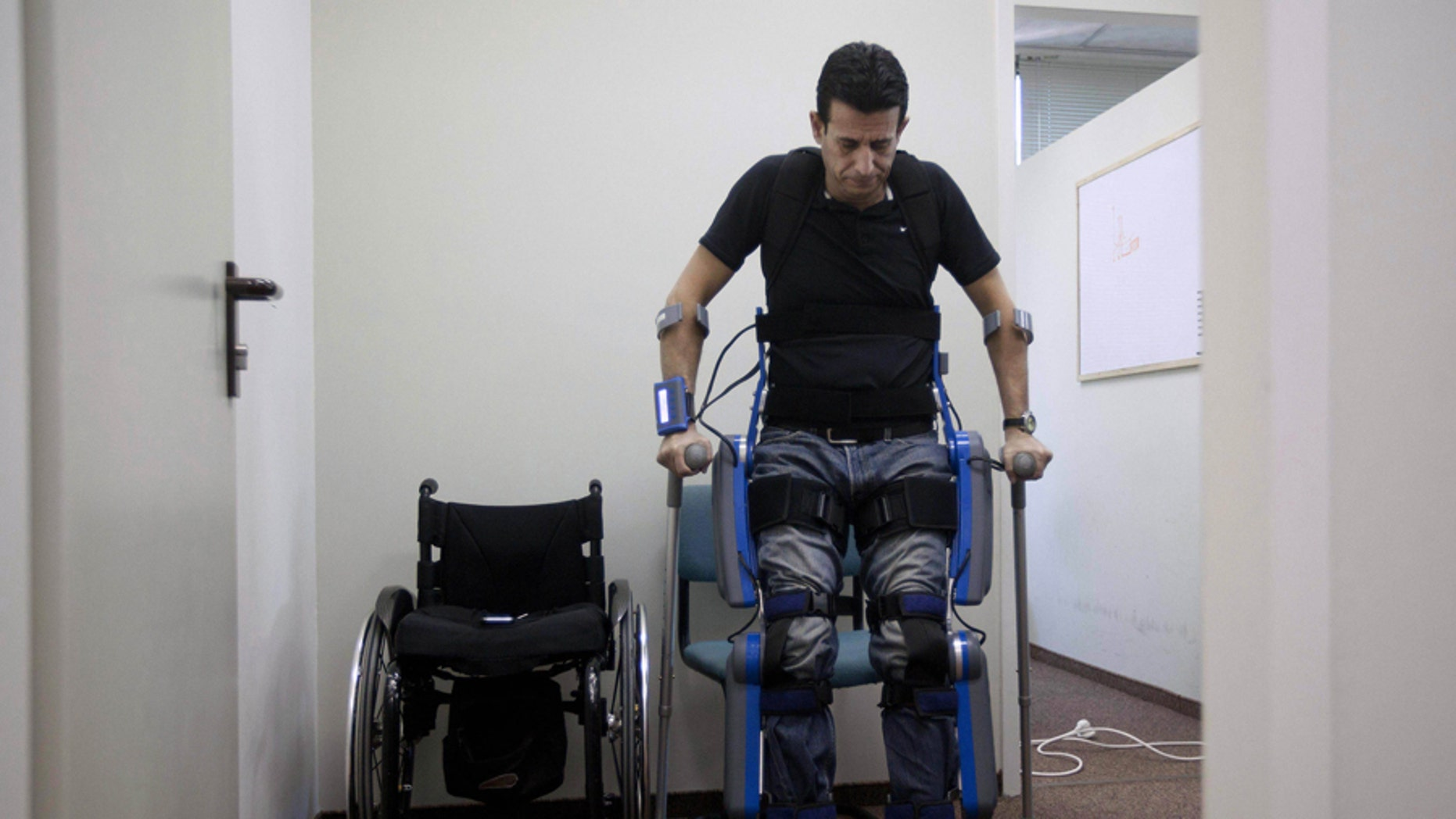 """Nov. 18: Radi Kaiuf, wounded and left paralyzed during his military service, gets up while strapped to """"ReWalk,"""" a device helping paralyzed patients stand and walk, in the northern Israeli town of Yokneam."""