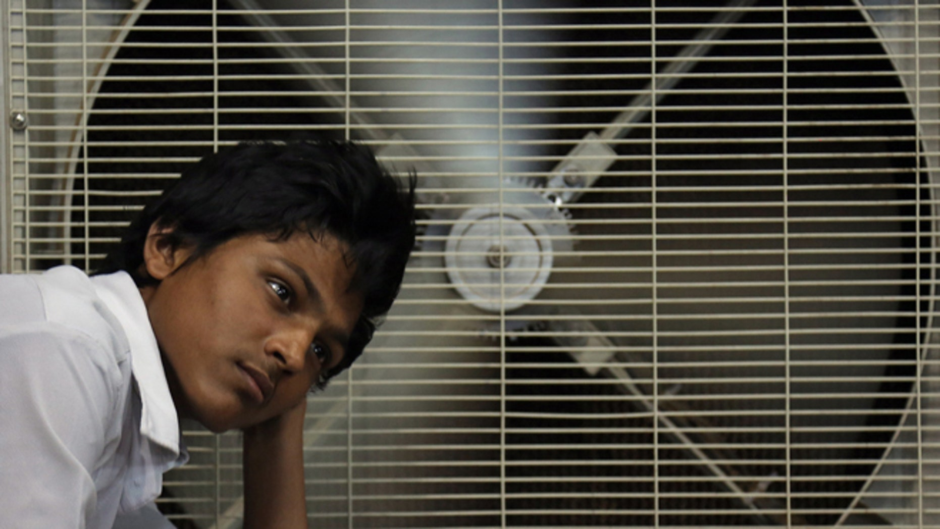 FILE - In this May 31, 2015 file photo, an Indian man rests in front of an air cooler to cool himself on a hot summer day in Hyderabad, in the southern Indian state of Telangana. Because of man-made global warming and a strong El Nino, Earths wild weather this year is bursting the annual heat record, the World Meteorological Organization announced Wednesday. (AP Photo/Mahesh Kumar A., File)