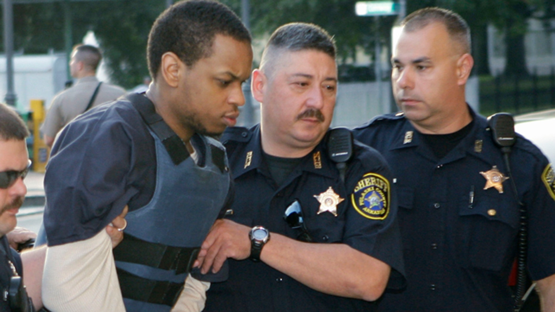 Abdulhakim Muhammad, second from left, is escorted to the Pulaski County Courthouse in Little Rock, Ark.