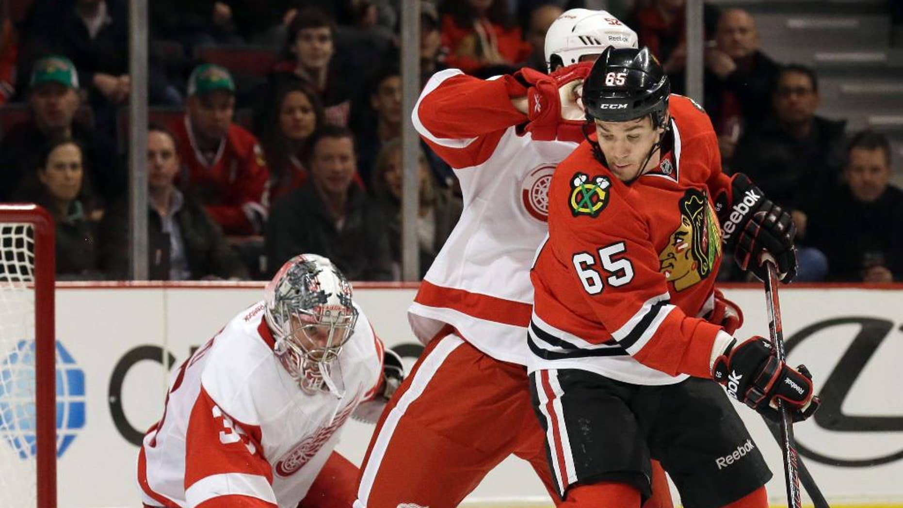 Chicago Blackhawks' Andrew Shaw (65), right, controls the puck against Detroit Red Wings' Jonathan Ericsson, center, and goalie Jimmy Howard (35) during the second period of an NHL hockey game in Chicago, Sunday, March 16, 2014. (AP Photo/Nam Y. Huh)