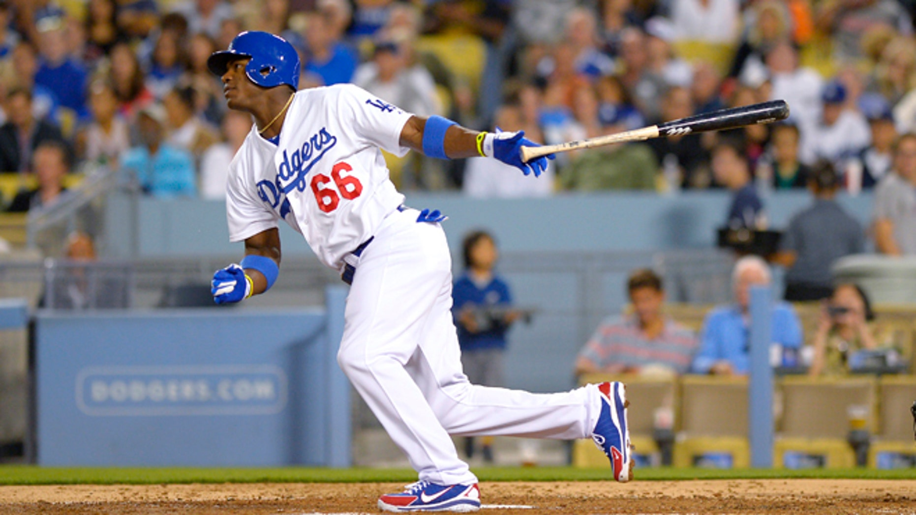 Los Angeles Dodgers Yasiel Puig watches his single in front of Cincinnati Reds catcher Devin Mesoraco during the fourth inning of a baseball game, Thursday, July 25, 2013, in Los Angeles. (AP Photo/Mark J. Terrill)