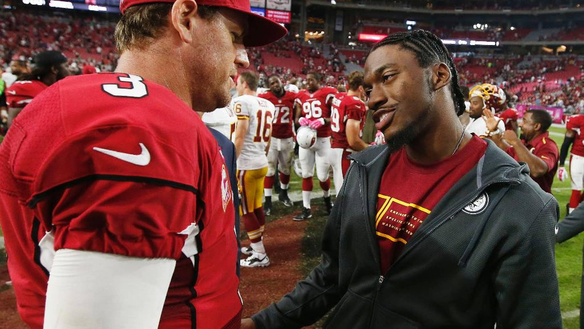 Injured Washington Redskins quarterback Robert Griffin III, right, talks with Arizona Cardinals quarterback Carson Palmer (3) after an NFL football game Sunday, Oct. 12, 2014, in Glendale, Ariz.  The Cardinals defeated the Redskins 30-20. (AP Photo/Ross D. Franklin)