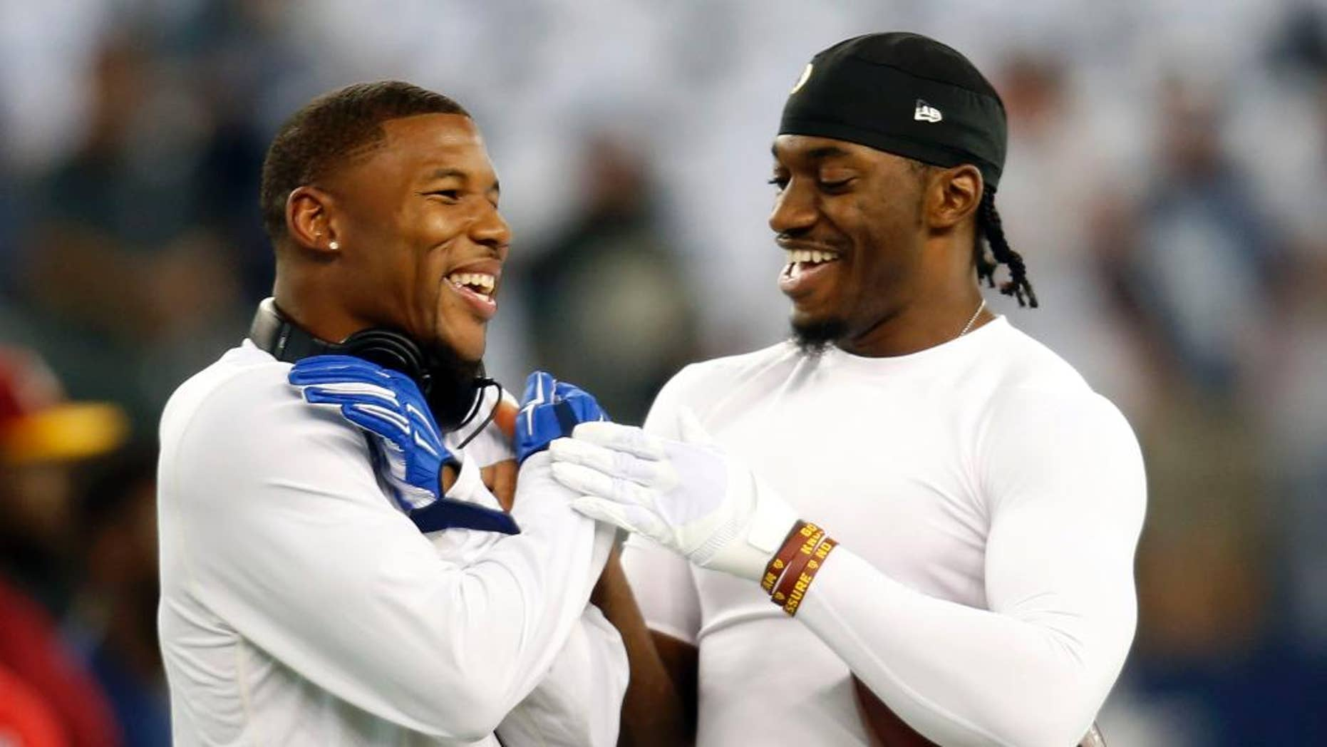 Dallas Cowboys wide receiver Terrance Williams, left, and Washington Redskins quarterback Robert Griffin III, right, greet each other on the field during warm ups before an NFL football game, Monday, Oct. 27, 2014, in Arlington, Texas. Williams and Griffin III played at Baylor University as teammates before entering the NFL. (AP Photo/Tim Sharp)