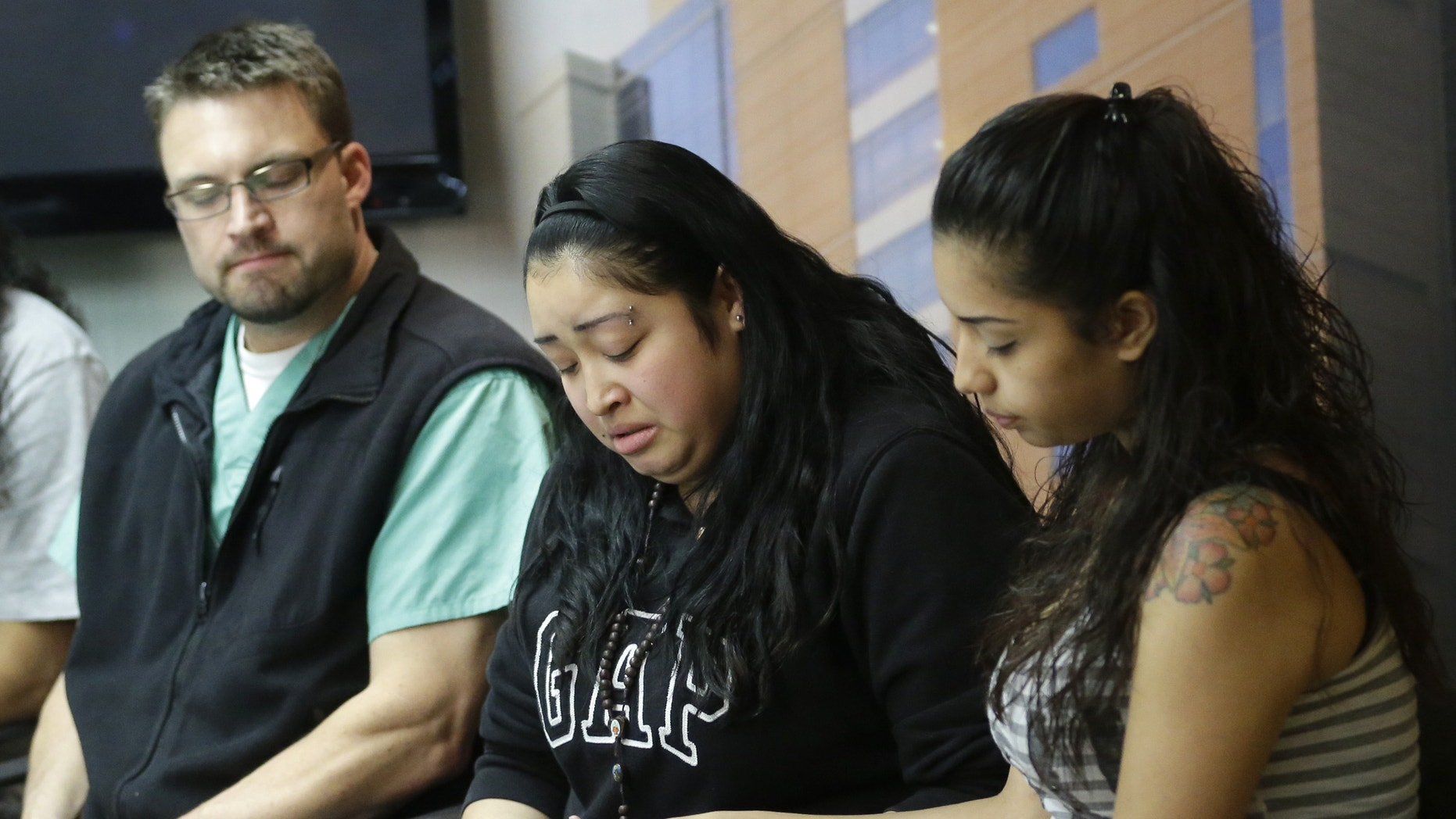 May 2, 2013: Johana Portillo, center, and her sister Ana Portillo hold hands while Dr. Shawn Smith looks on during a news conference at Intermountain Medical Center, in Murray, Utah. Ricardo Portillo, a Utah soccer referee, is in a coma after being punched by a teenage player unhappy with one of his calls, and his family says their only hope is for a miracle.