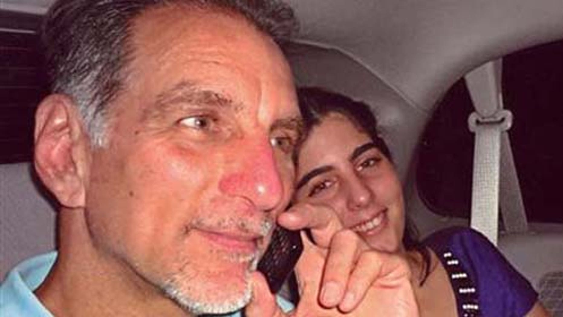 Oct. 12, 2011: In this photo released on Wednesday by the state media Cubadebate website, convicted Cuban agent René González talks on the phone accompanied by his youngest daughter Ivette, after he was freed from a Florida jail, after serving 13 years of a 15-year sentence, in Marianna, Fla.