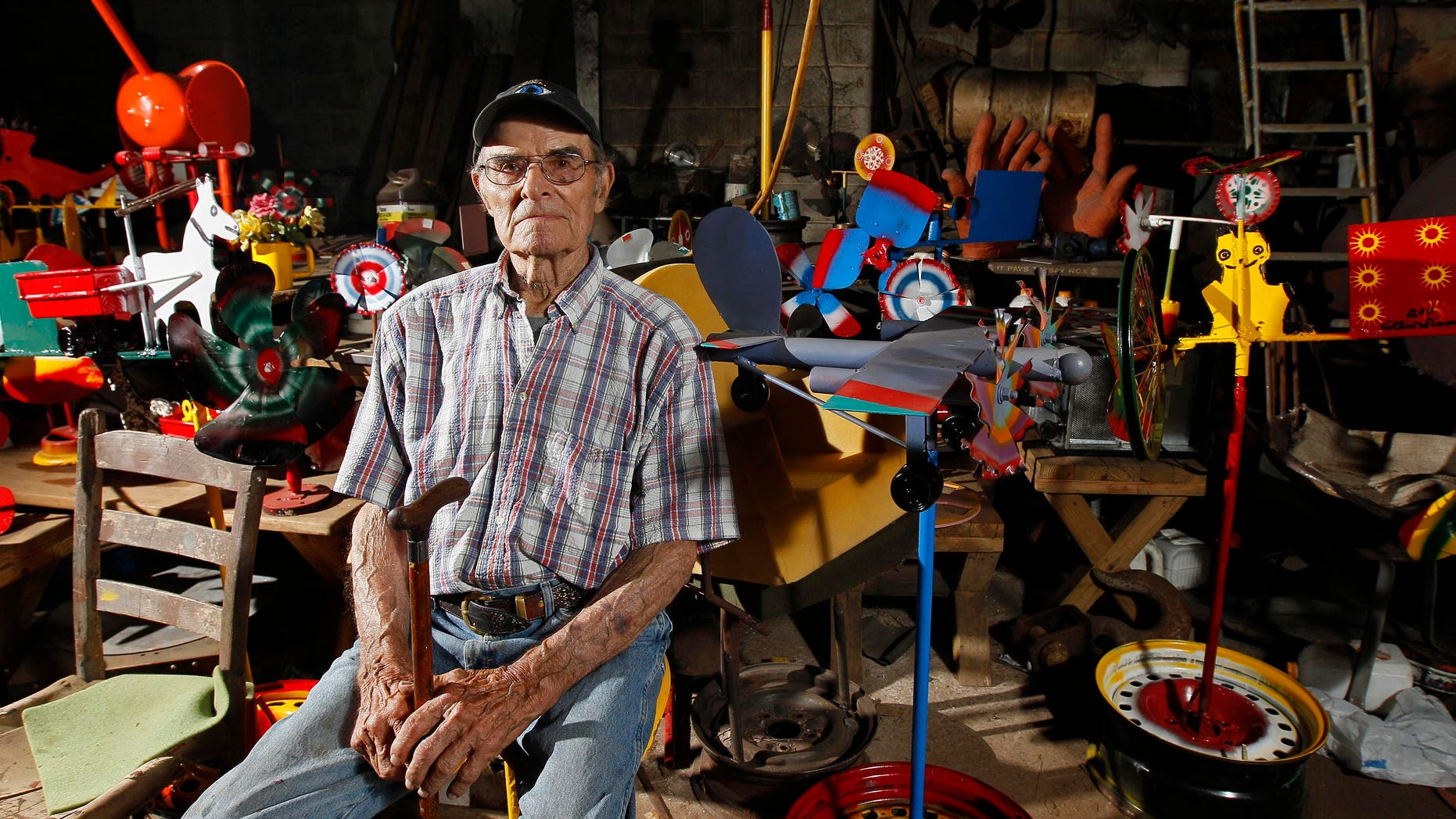 In this photo taken  Thursday, June 21, 2012, whirligig artist Vollis Simpson sits in his shop surrounded by his whirligigs in Lucama, N.C., Thursday, June 21, 2012. In a huge warehouse a few miles from where Simpson's whirligigs have stood for years, people spend their days repairing the wind-driven creations, giving them the same attention that one gives a Picasso. They're repairing the whirligigs in advance of moving them next year to a downtown park. (AP Photo/Gerry Broome)