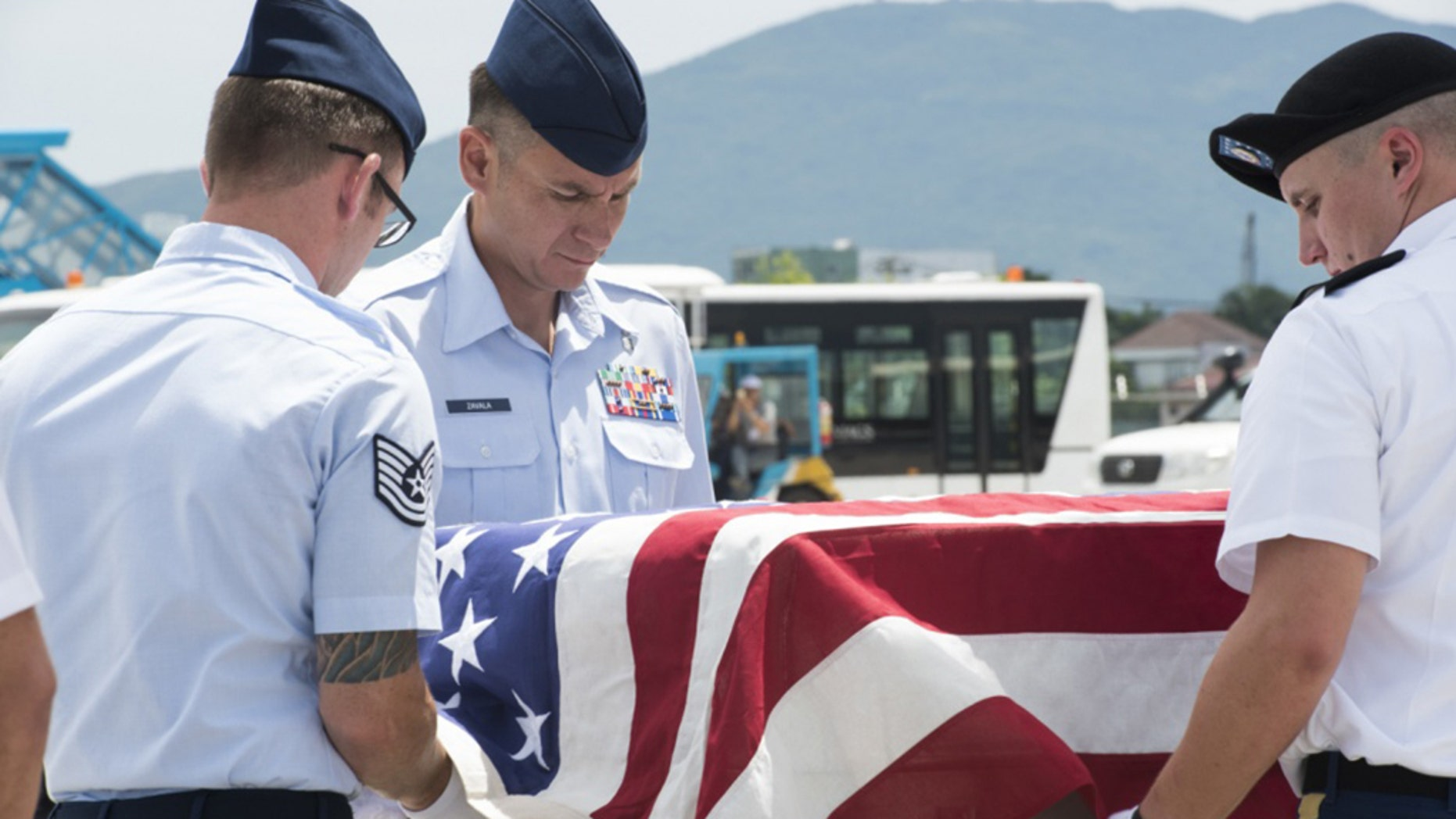 U.S. service members assigned to the Defense POW/MIA Accounting Agency (DPAA), drape a transfer case with the American flag during a repatriation ceremony, Da Nang, Socialist Republic of Vietnam, July 8, 2018.