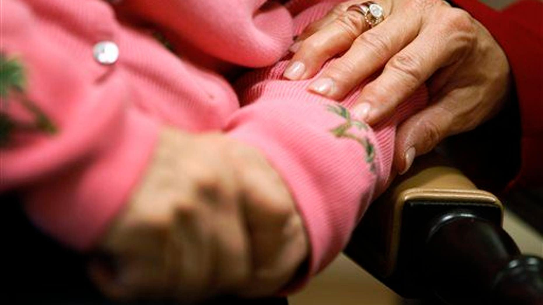In this Feb. 6, 2012, file photo, a worker at an Alzheimer's assisted-living site puts her hand on the arm of a resident.