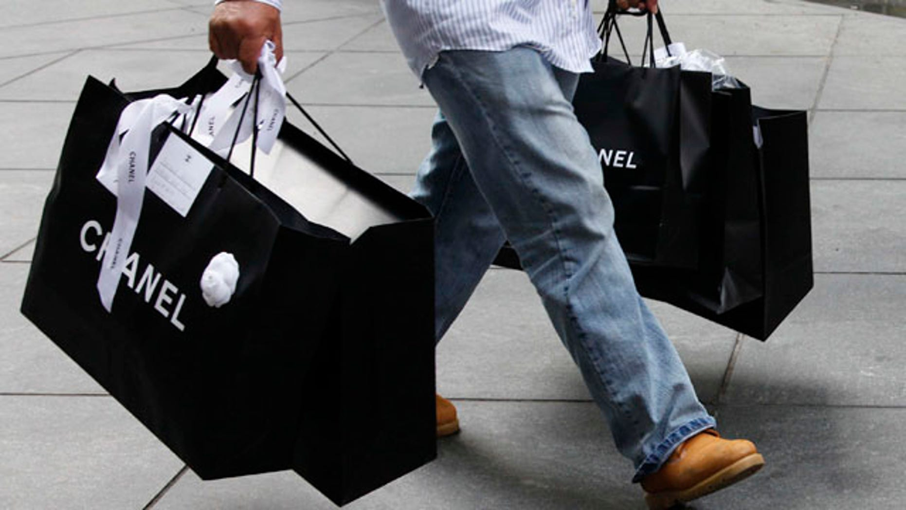 Oct. 25: A man carries Chanel shopping bags in New York. Retail sales increased in October by the largest amount since March, easing worries over the economic recovery.