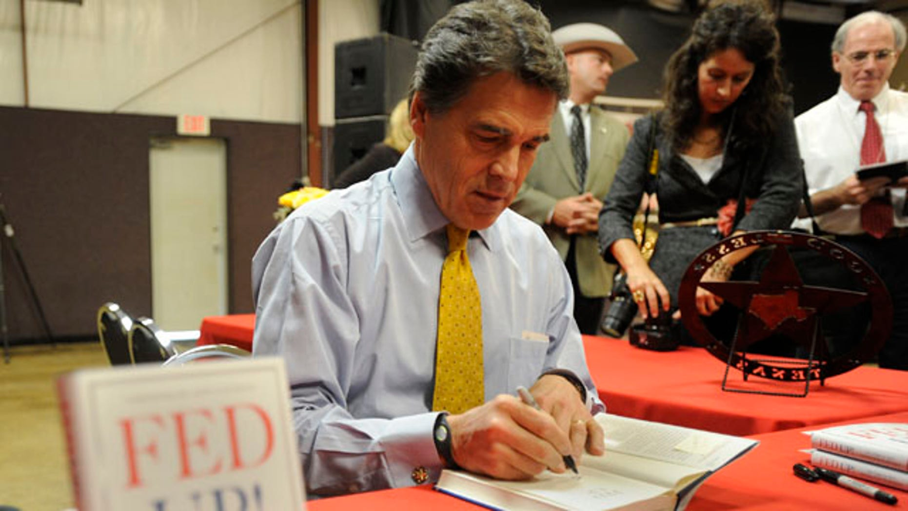 "Nov. 12: Texas Gov. Rick Perry signs copies of his book ""Fed Up!"" during a stop in Tyler, Texas."