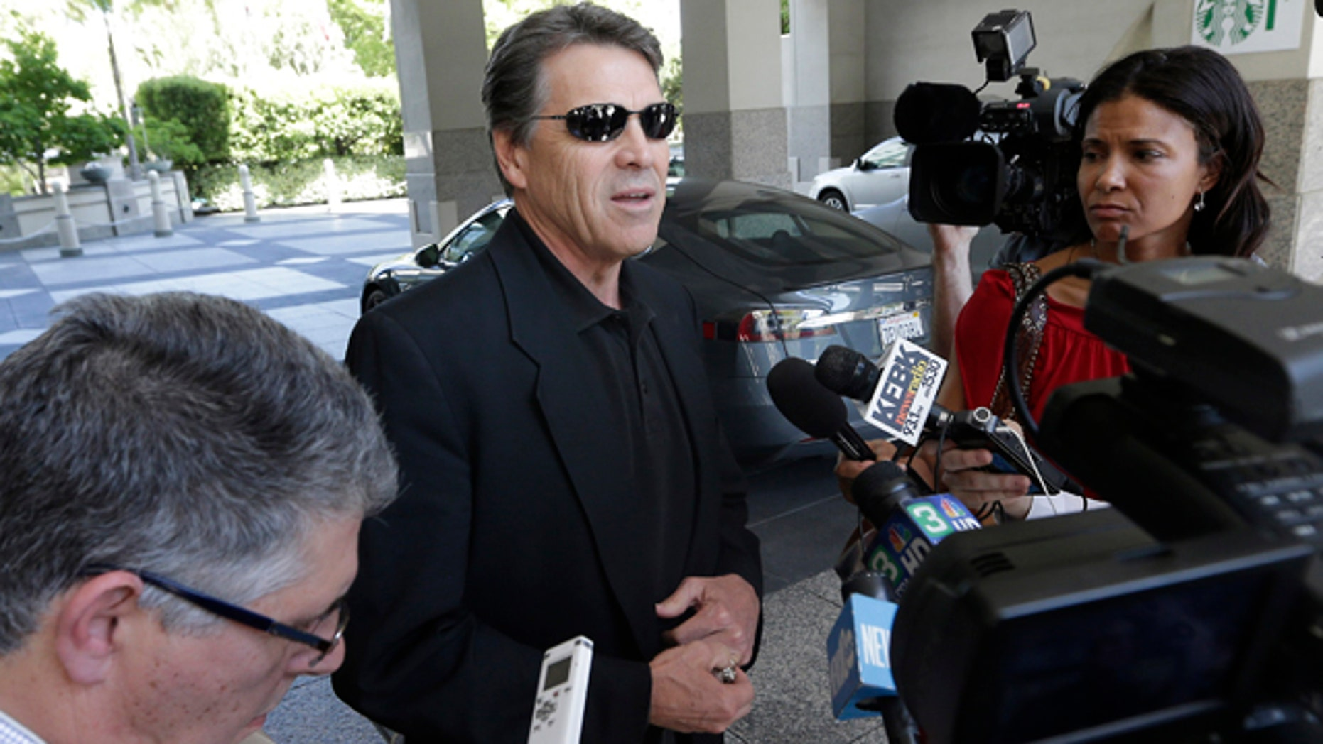 June 10, 2014: Texas Gov. Rick Perry, center, talks to reporters after driving up in a Tesla Motors Type S electric car in Sacramento, Calif. (AP Photo/Rich Pedroncelli)
