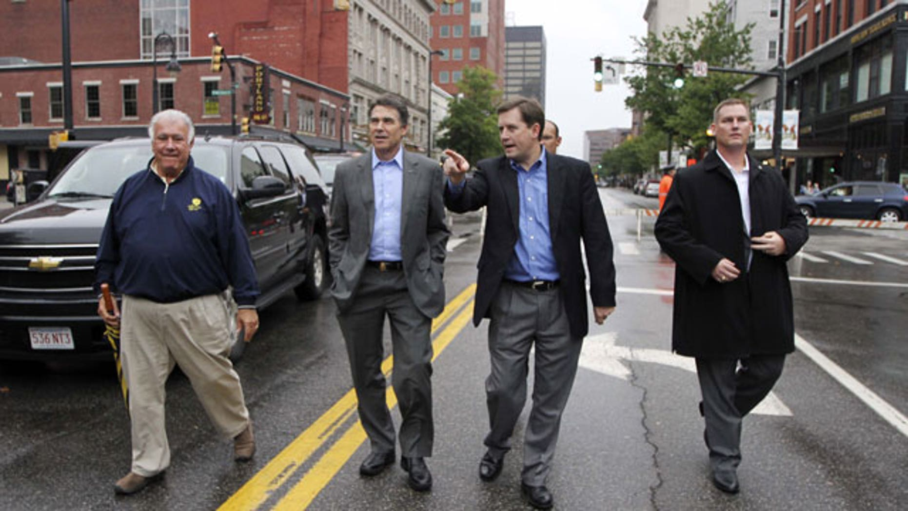 October 5: Republican presidential candidate, Texas Gov. Rick Perry, second from left, arrives at the Chili Festival with Mayor Ted Gatsas, far left, in Manchester, N.H.