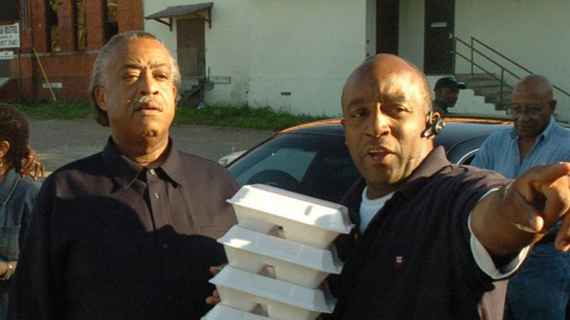 The Rev. Al Sharpton, left, is seen with Kenneth Glasgow, as they deliver holiday meals on Thanksgiving Day in 2006 in Dothan, Ala.