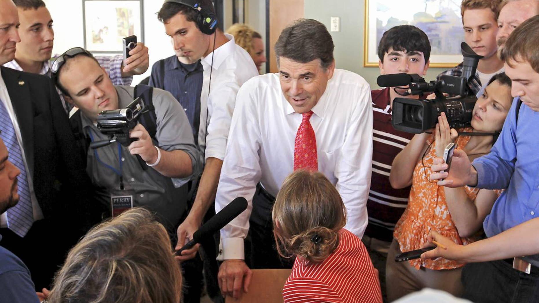 Republican presidential candidate, Texas Gov. Rick Perry talks with locals in a cafe during a visit to downtown Portsmouth, N.H., Thursday, Aug. 18, 2011. (AP Photo/Cheryl Senter)