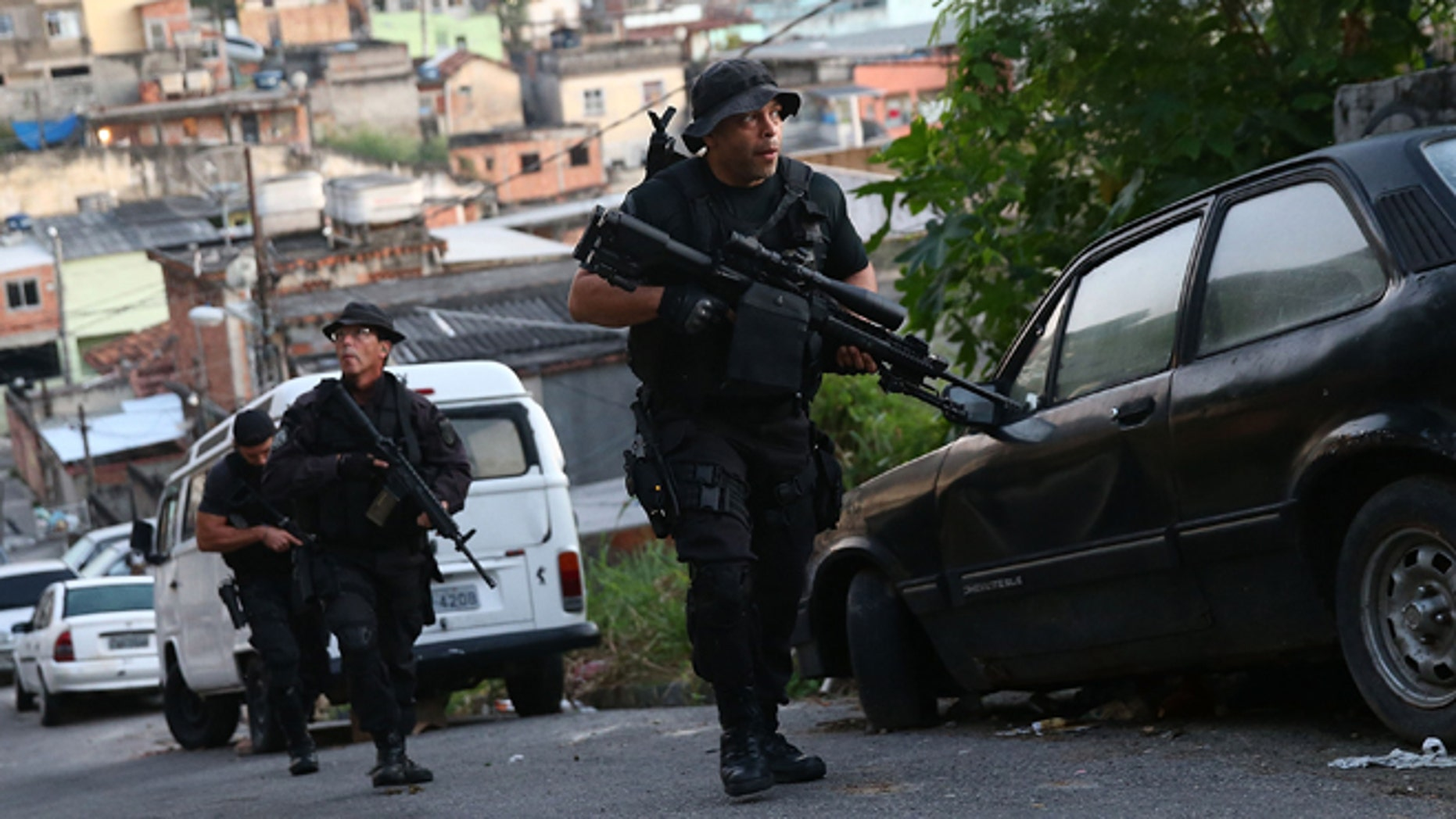 RIO DE JANEIRO, BRAZIL - MAY 13:  Officers from the CORE police special forces patrol during an operation to search for fugitives in the Complexo do Alemao pacified community, or 'favela' on May 13, 2014 in Rio de Janeiro, Brazil. Ahead of the 2014 FIFA World Cup, Rio has seen an uptick in violence in its pacified slums. A total of around 1.6 million Rio residents live in shantytowns, many of which are controlled by drug traffickers.  (Photo by Mario Tama/Getty Images)