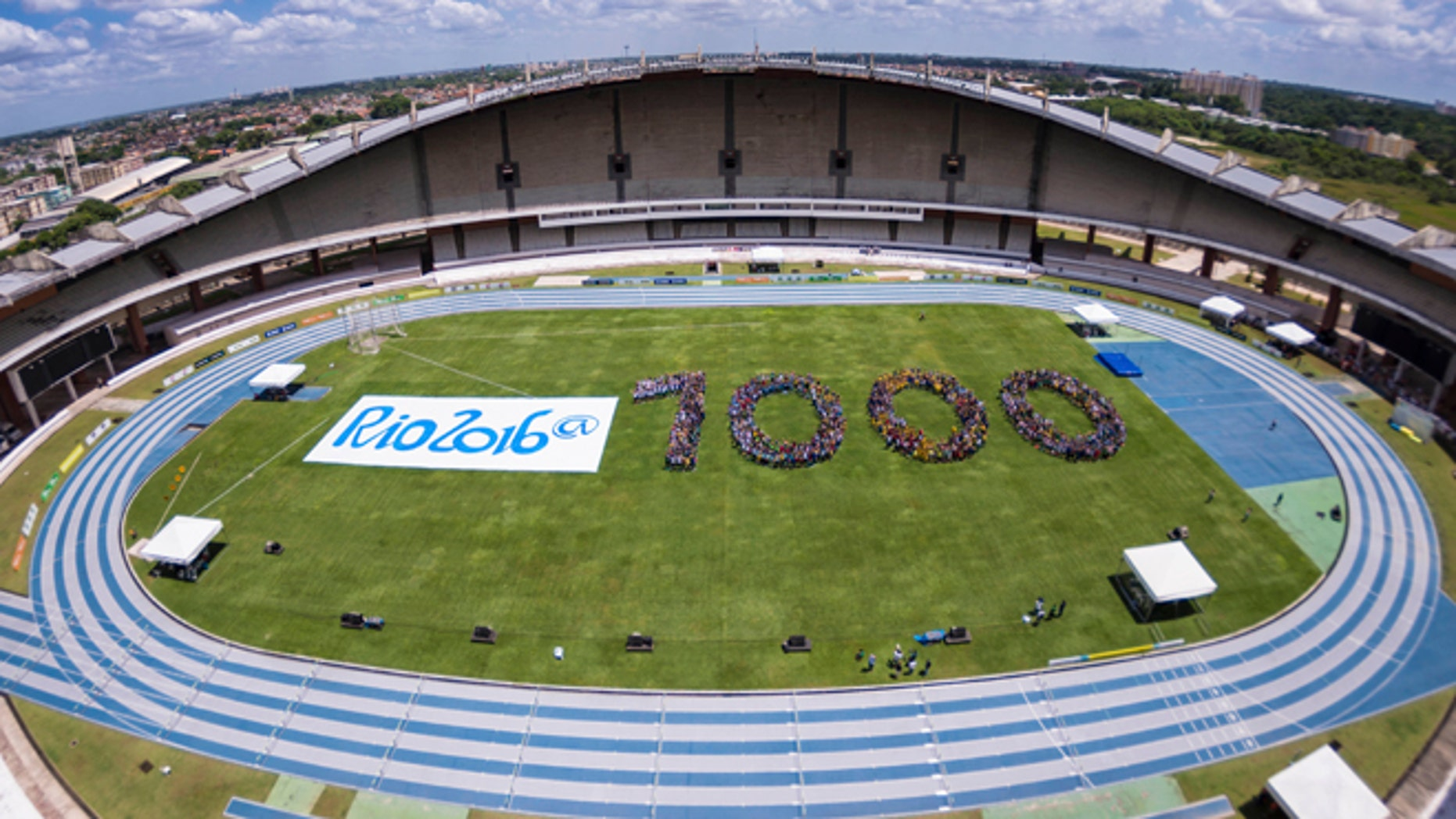 In this photo released by Rio 2016 Organizing Committee for the Olympic and Paralympic Games, youths form the number 1,000 to mark the number of days before the start of the Rio 2016 Olympic Games inside Mangueirao stadium in Belém, Brazil, Friday, Nov. 8, 2013. (AP Photo/Alex Ferro, Rio 2016 Organizing Committee for the Olympic and Paralympic Games)