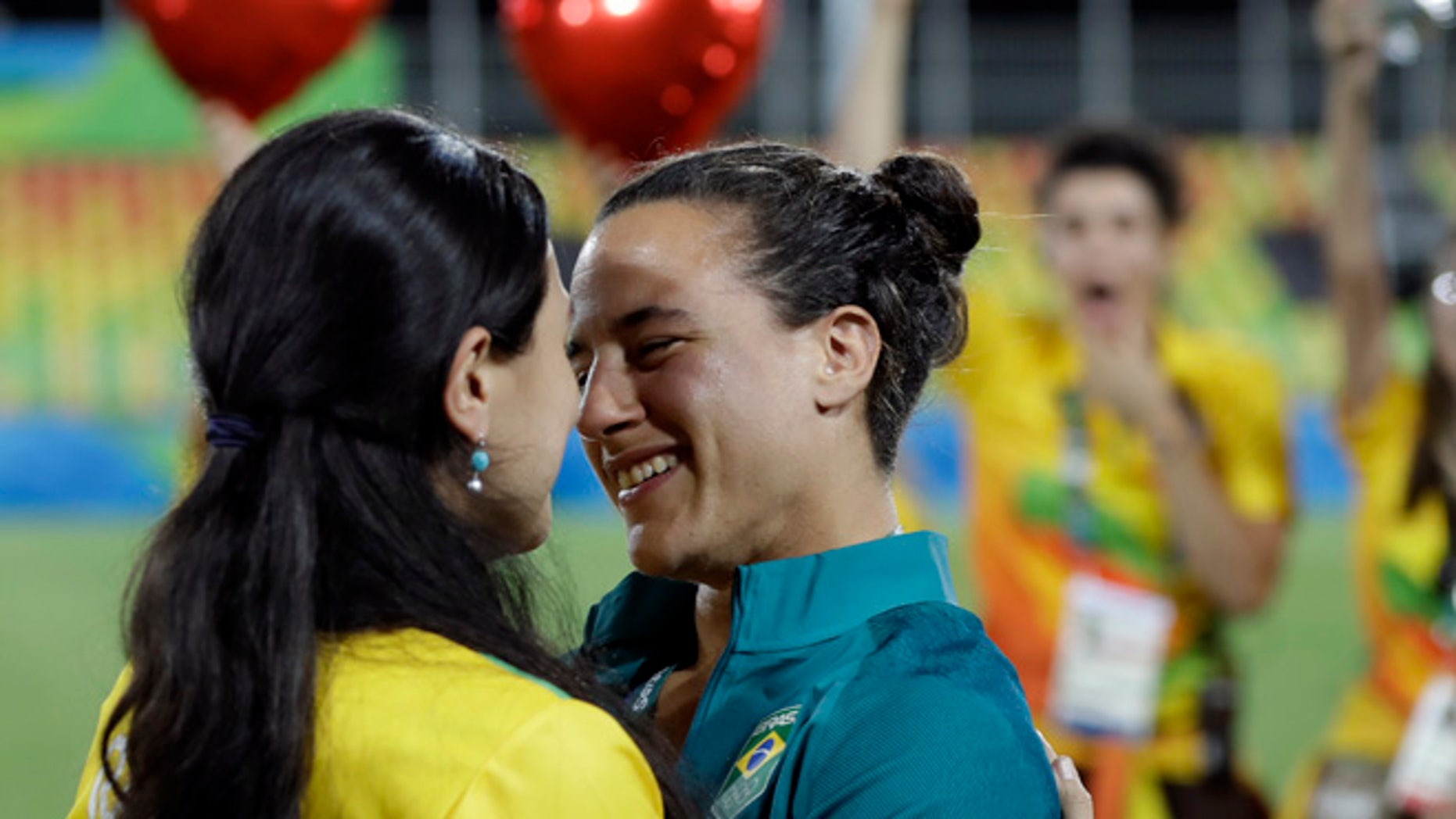 Brazil's Isadora Cerullo, right, shares a moment with her partner Marjorie Enya, after she was asked her to marry her, after the medal ceremony for the women's rugby sevens match at the Summer Olympics in Rio de Janeiro, Brazil, Monday, Aug. 8, 2016. (AP Photo/Themba Hadebe)