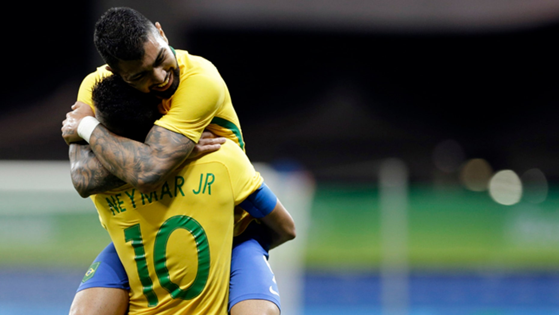 Brazil's Gabriel Barbosa celebrates with teammate Neymar after scoring his team's first goal during a group A match of the men' s Olympic football tournament between Brazil and Denmark in Salvador, Brazil, Wednesday Aug. 10, 2016.(AP Photo/Leo Correa)