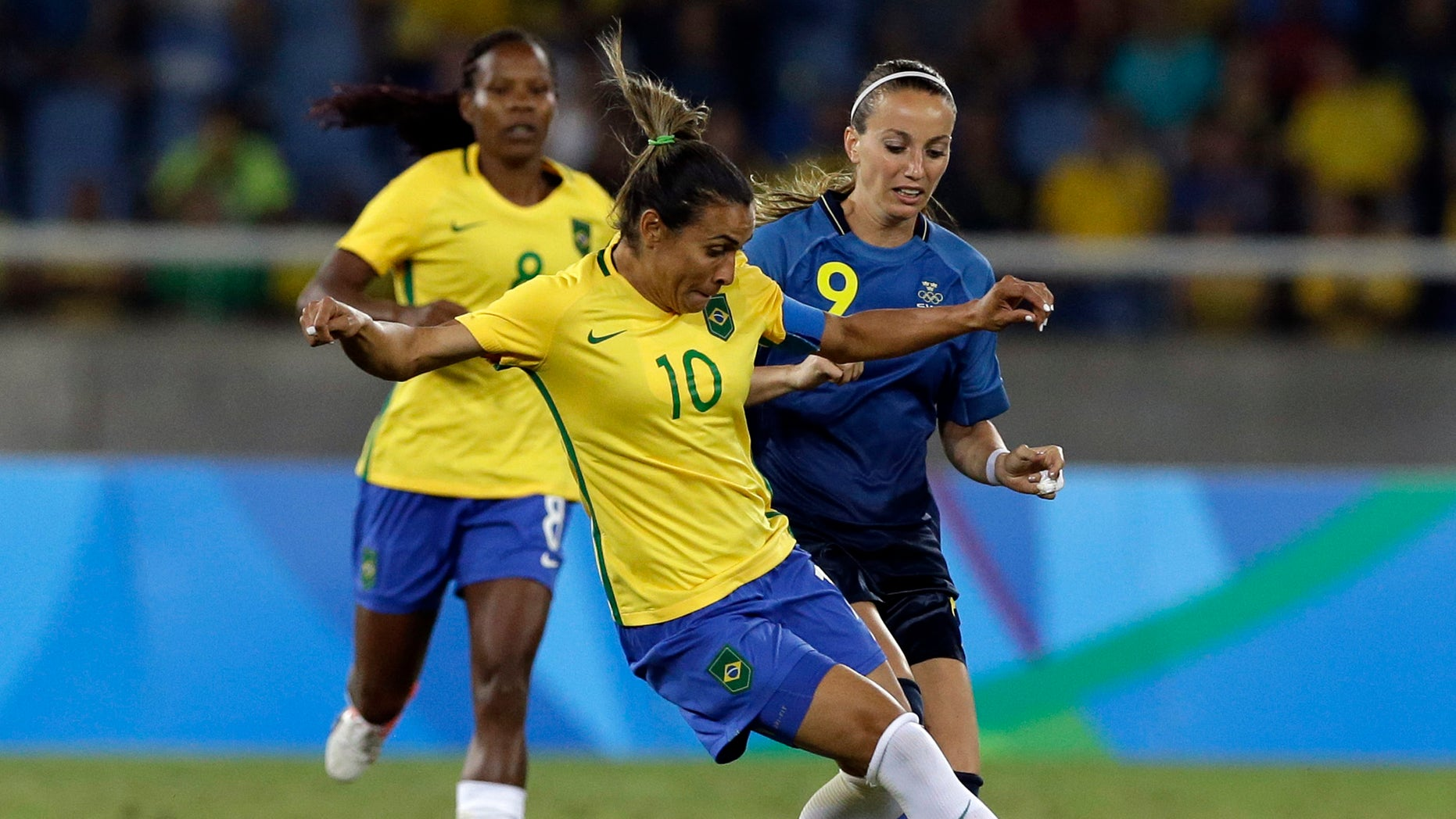 Brazil's Marta, center, dribbles past Sweden's Kosovare Asllani during a group E match of the women's Olympic football tournament between Sweden and Brazil at the Rio Olympic Stadium in Rio De Janeiro, Brazil, Saturday, Aug. 6, 2016. (AP Photo/Leo Correa)