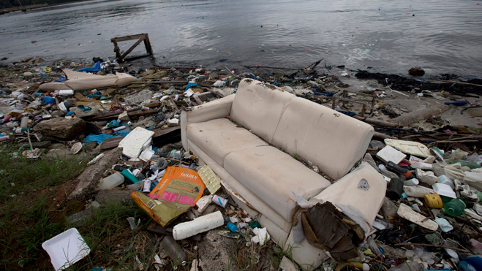 In this June 1, 2015 file photo, a discarded sofa litters the shore of Guanabara Bay in Rio de Janeiro, Brazil. As part of its Olympic bid, Brazil promised to build eight treatment facilities to filter out much of the sewage and prevent tons of household trash from flowing into the Guanabara Bay. Only one has been built. Tons of household trash line the coastline and form islands of refuse. (AP Photo/Silvia Izquierdo, File)