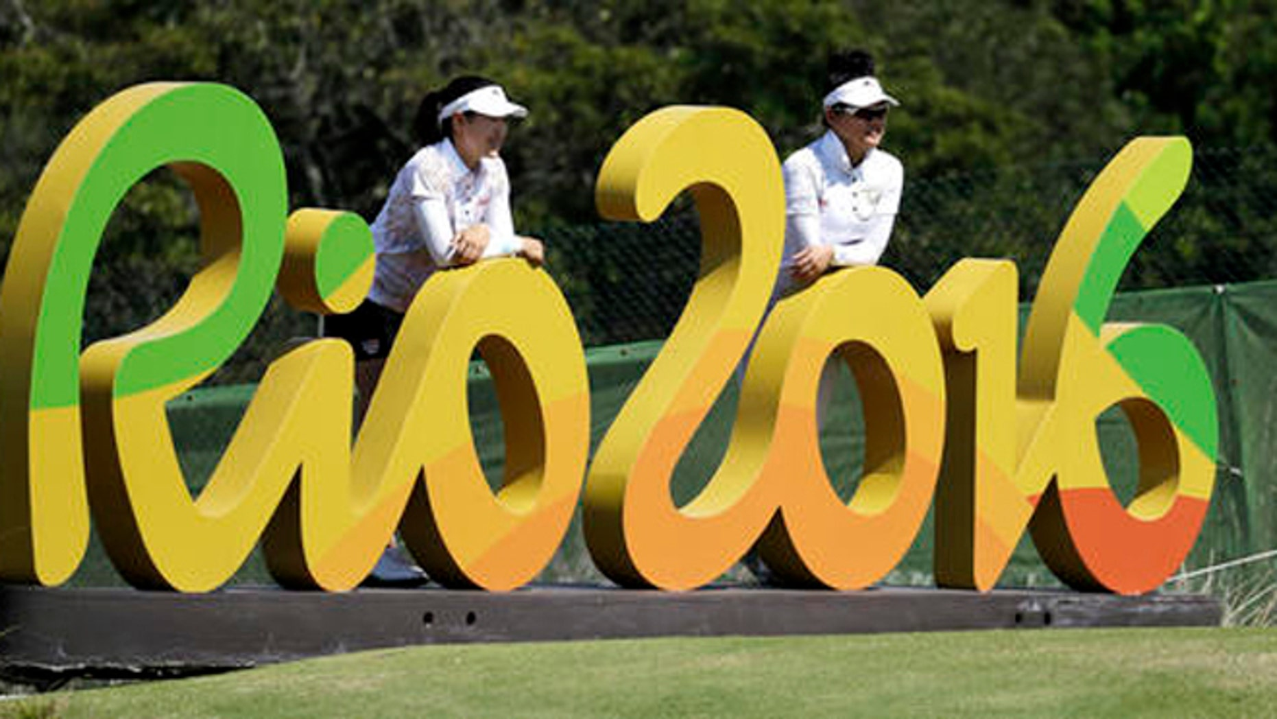 FILE  - In this Aug.16, 2016 file photo, Kelly Tan, left, and Michelle Koh both of Malaysia, pose for a photo with the Rio 2016 logo on the 16th hole during a practice round for the women's golf event at the 2016 Summer Olympics in Rio de Janeiro, Brazil. The Rio Olympics could leave behind at least one unexpected legacy _ a new home for the consular office of the United States. The headquarters of the Rio de Janeiro Olympic organizing committee in central Rio will be abandoned in the next few weeks with staff moving to smaller quarters in downtown Rio.   (AP Photo/Chris Carlson, File)