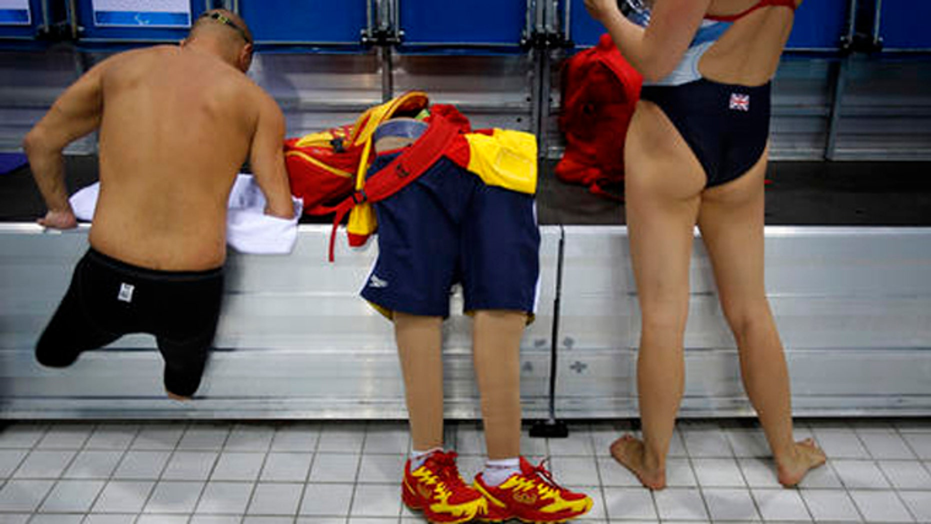 FILE - In this Aug. 31, 2012 file photo, Spain's Xabi Torres jumps next to his prosthesis as he leaves the swimming pool after training ahead of the competition at the 2012 Paralympics Olympics in London.  The countdown clock for the Paralympic Games in Rio reaches 100 days on Monday with about 4,300 athletes participating, far fewer than the 10,500 in the Olympics. The Paralympic Games open Sept. 7.(AP Photo/Emilio Morenatti, File)