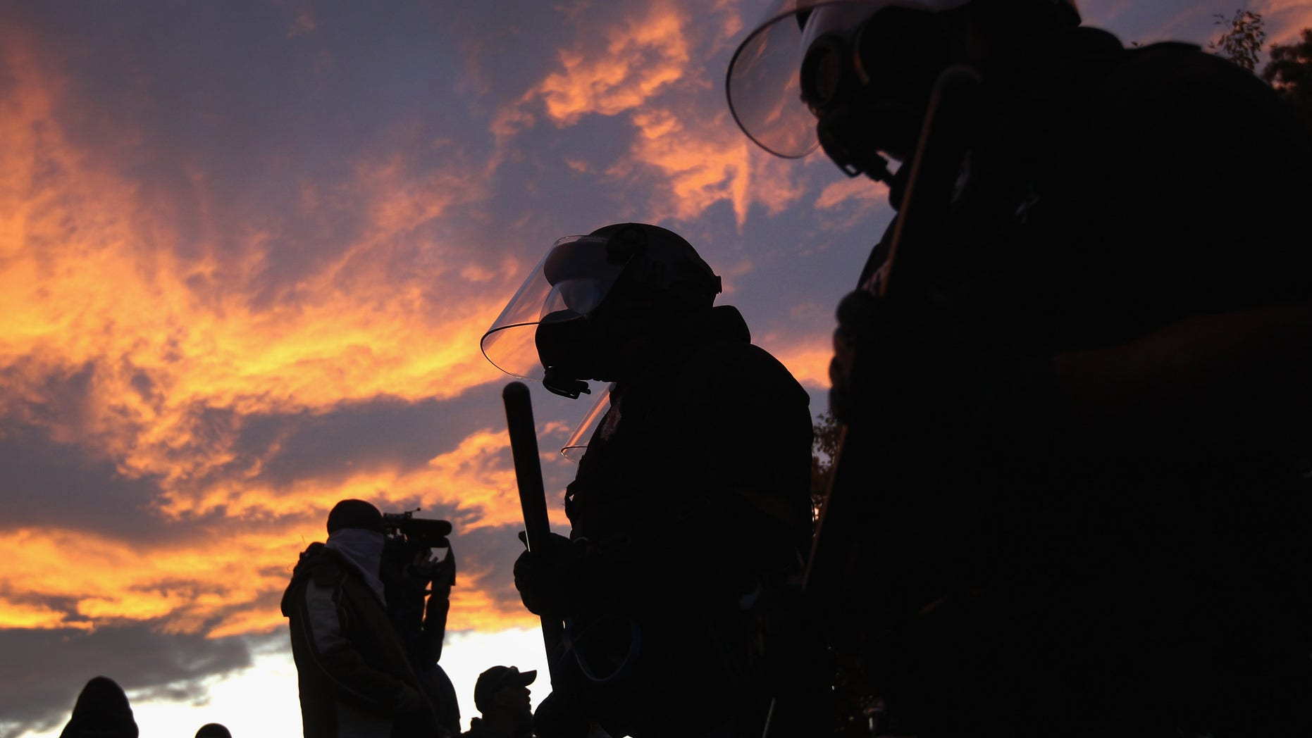 """DENVER, CO - OCTOBER 29:  Riot police face off with demonstrators at the """"Occupy Denver"""" camp on October 29, 2011 in Denver, Colorado. Following a march by protesters, police moved in on their encampment to tear down recently erected tents. They arrested numerous protesters, pepper-sprayed others and others reportedly fired rubber bullets at the crowd during the confrontation.  (Photo by John Moore/Getty Images)"""