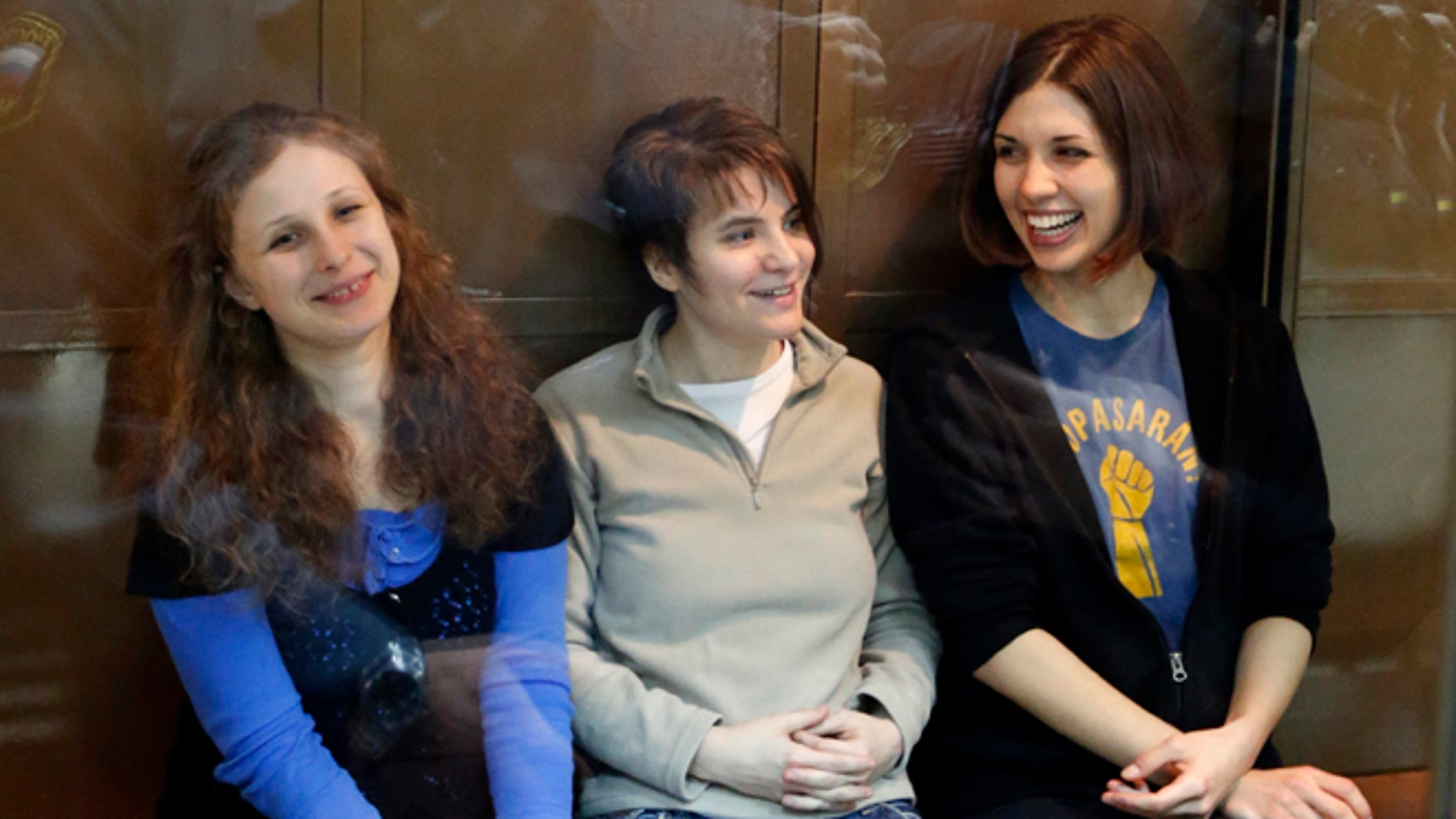 In this Oct. 1, 2012 file photo, feminist punk group Pussy Riot members, from left, Maria Alekhina, Yekaterina Samutsevich and Nadezhda Tolokonnikova sit in a glass cage at a court room in Moscow, Russia. Alekhina went on hunger strike May 22, 2013, in protest at not being allowed to attend her own parole hearing in Perm province.