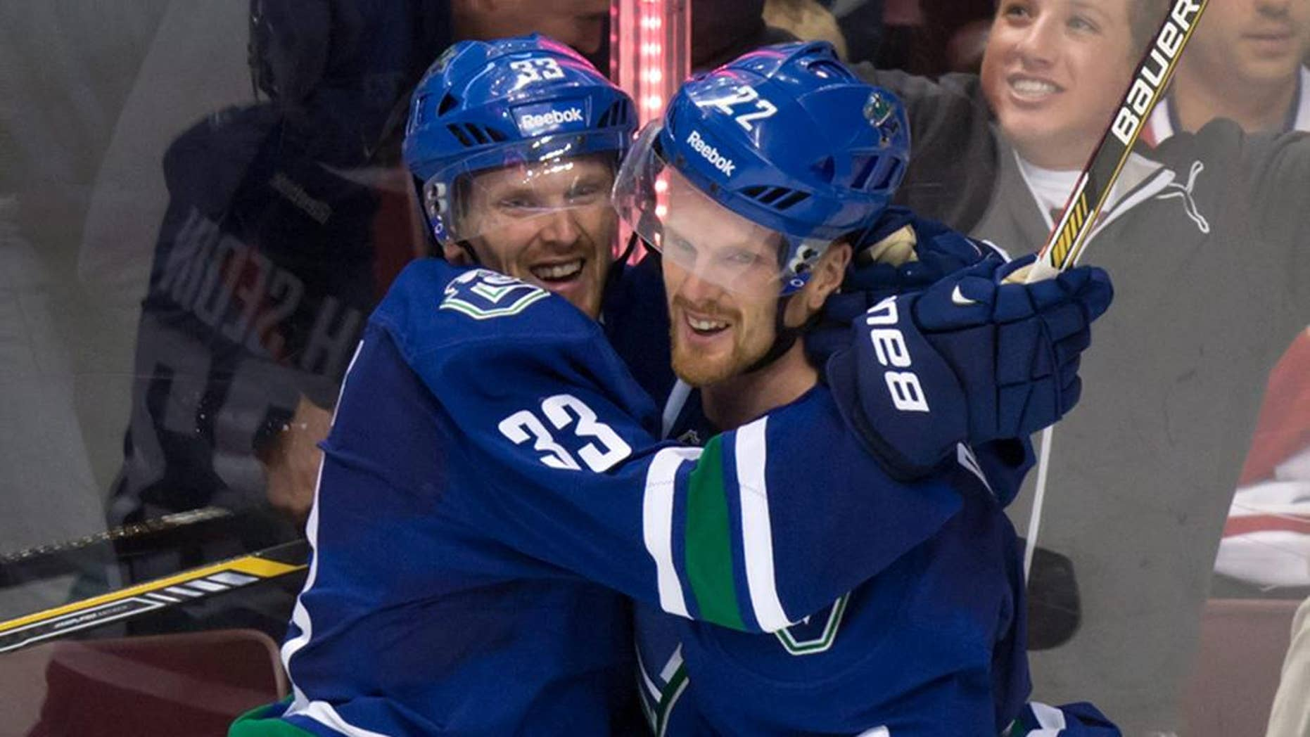 FILE - This Oct. 30, 2014, file photo shows Vancouver Canucks' Daniel Sedin, right, celebrating with his twin brother Henrik Sedin, both of Sweden, after scoring the winning goal against the Montreal Canadiens at an NHL hockey game in Vancouver. After the Canucks missed the playoffs last spring, they overhauled their front office and stripped their roster to its foundation, the Sedin twins. Many expected a lengthy rebuild but the revamped Canucks are off to a sizzling start in the Pacific Division. (AP Photo/The Canadian Press,  Darryl Dyck,File)