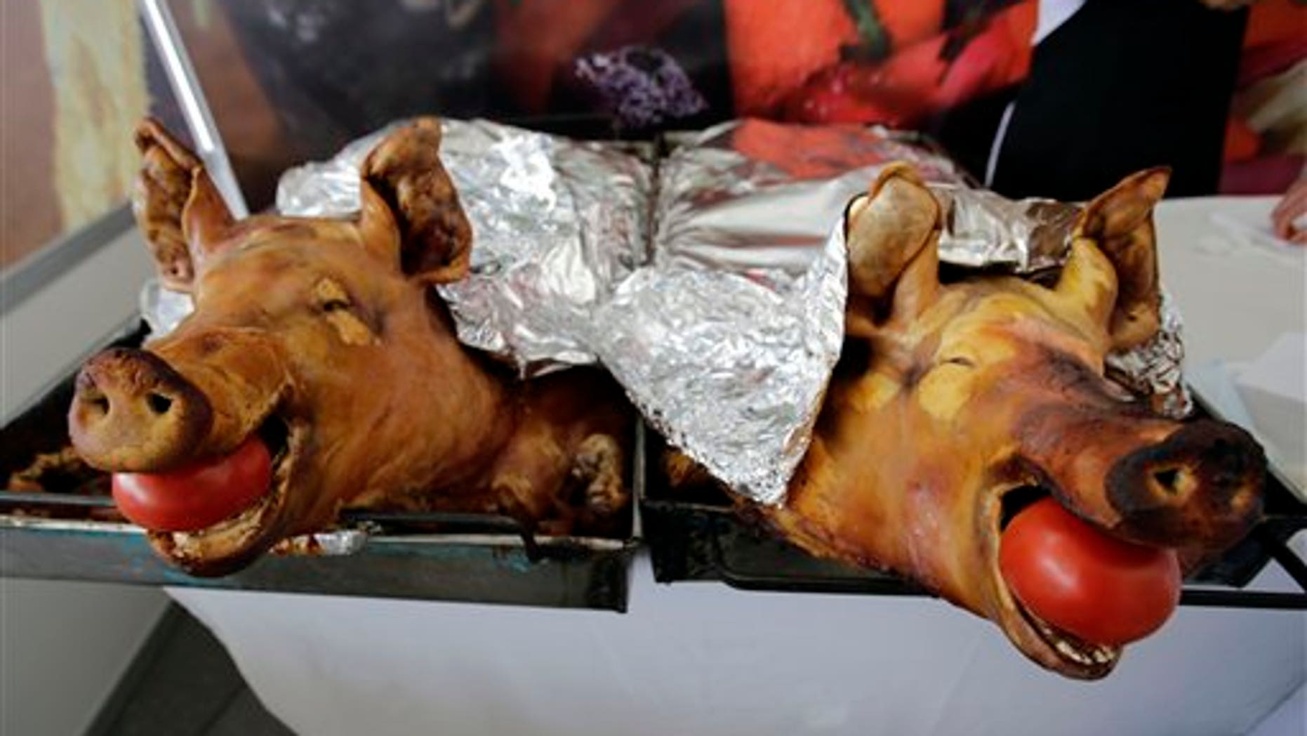 """In this Aug. 17, 2014 photo, slow-roasted pork known as """"Hornado,"""" a traditional dish consisting of marinated, slow-roasted pork, is presented before the judges of the national contest to choose the country's best """"Hornado,"""" in Riobamba, Ecuador. After years of disputes within the different regions of Ecuador, over who could make the best """"Hornado,"""" the championship on Sunday finally settled the issue. (AP Photo/Dolores Ochoa)"""