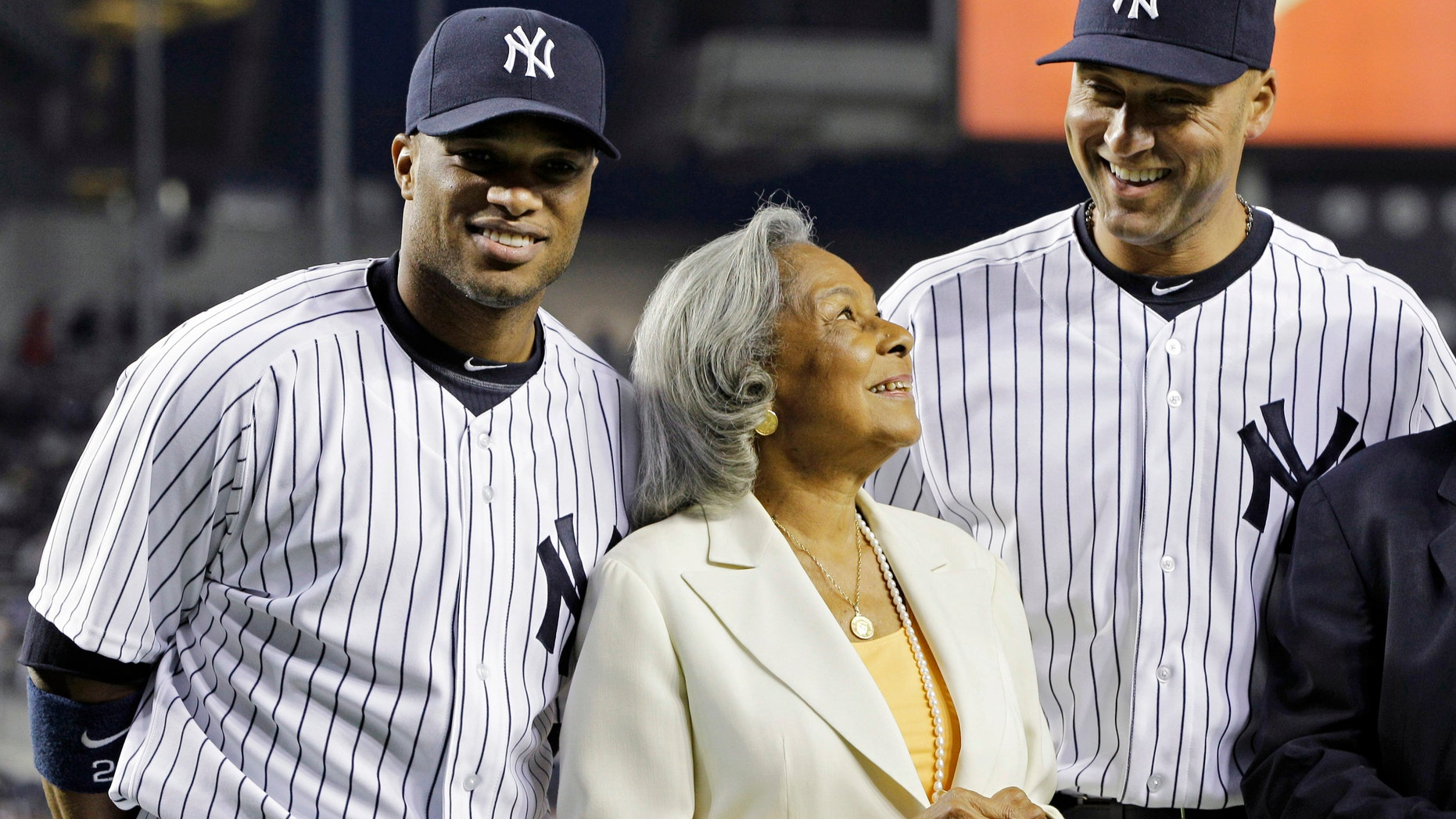 New York Yankees second baseman Robinson Cano, left, and shortstop Derek Jeter join Rachel Robinon, widow of Jackie Robinson, on the field prior to the Yankees' baseball game against the Los Angeles Angels on Jackie Robinson Day at Yankee Stadium in New York, Sunday, April 15, 2012. (AP Photo/Kathy Willens)