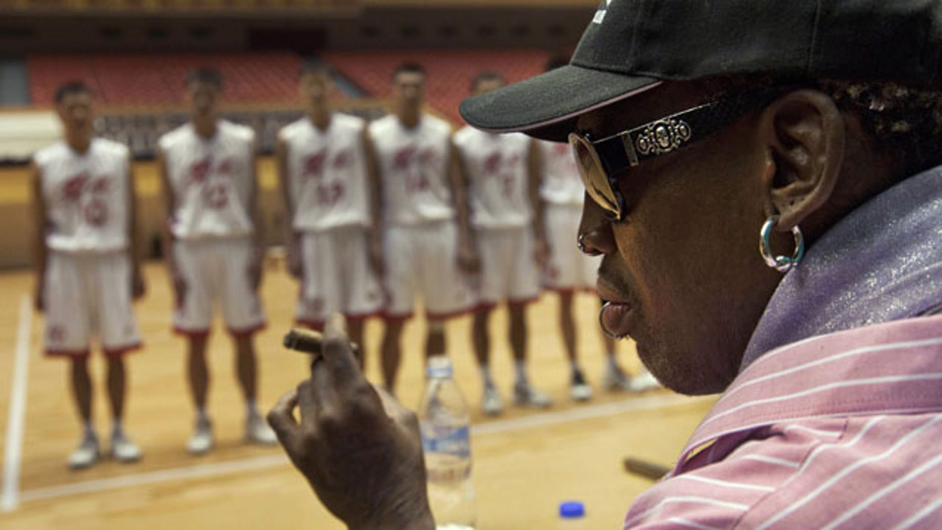 December 20, 2013: Former NBA basketball player Dennis Rodman holds a cigar as he speaks to North Korean basketball players during a practice session in Pyongyang, North Korea. During the session, Rodman selected the members of the North Korean team who will play in Pyongyang against visiting NBA stars on Jan. 8, 2014, the birthday of North Korean leader Kim Jong Un. (AP)