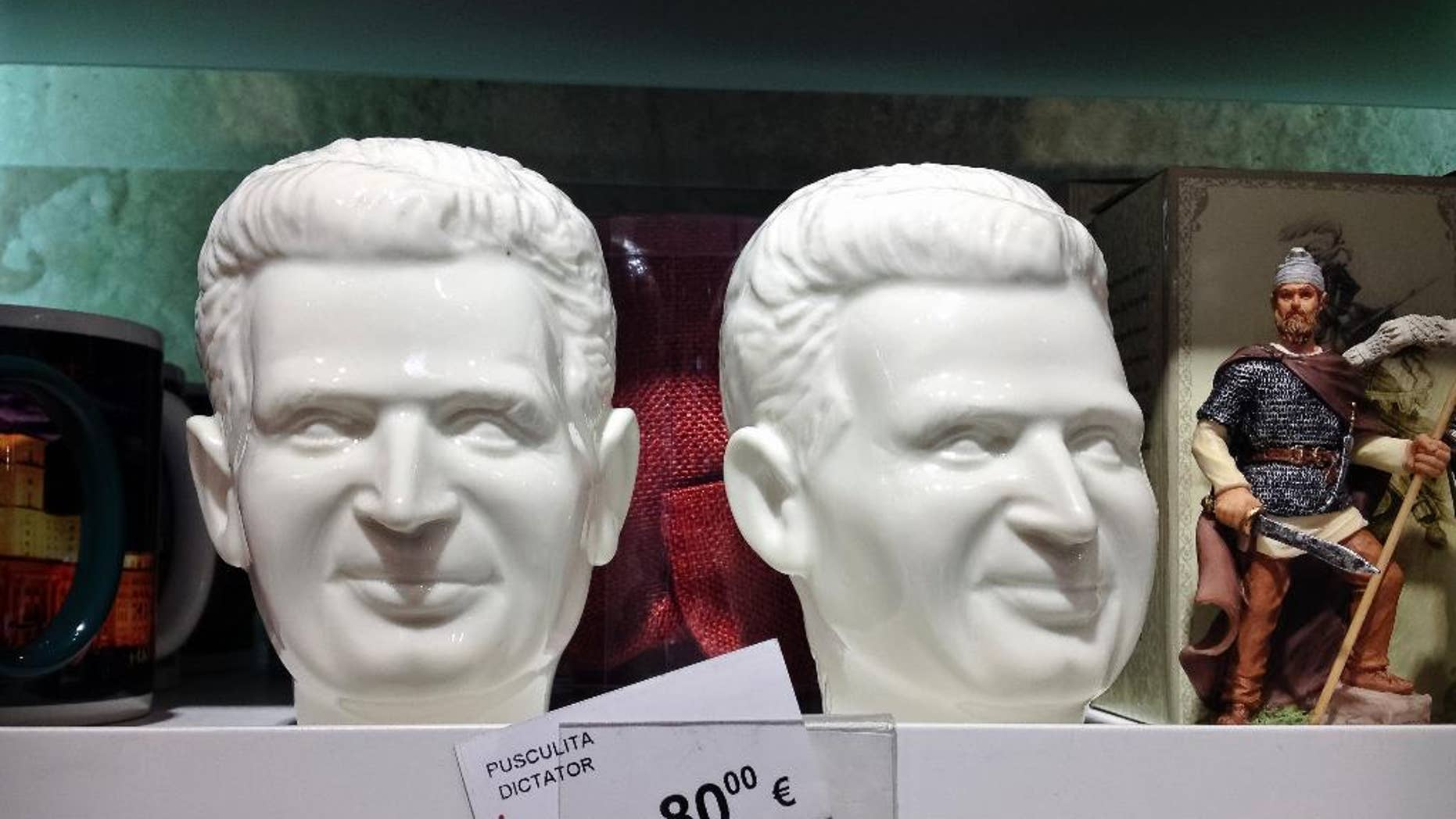 A picture taken on Dec. 7, 2014 shows a porcelain piggybank representing communist dictator Nicolae Ceausescu, next to legendary ancient and medieval kings representations on sale in the duty free shop of the Henri Coanda international airport in Otopeni, Romania. Romanians, especially those of a more senior age, have mixed feelings about the former dictator and his rule, 25 years after his execution, with many remembering predominantly the positive aspects, like the social security, of the communist times and not focusing on the extreme economic hardships and lack of basic human rights of that period, like freedom of movement or speech.(AP Photo/Vadim Ghirda)