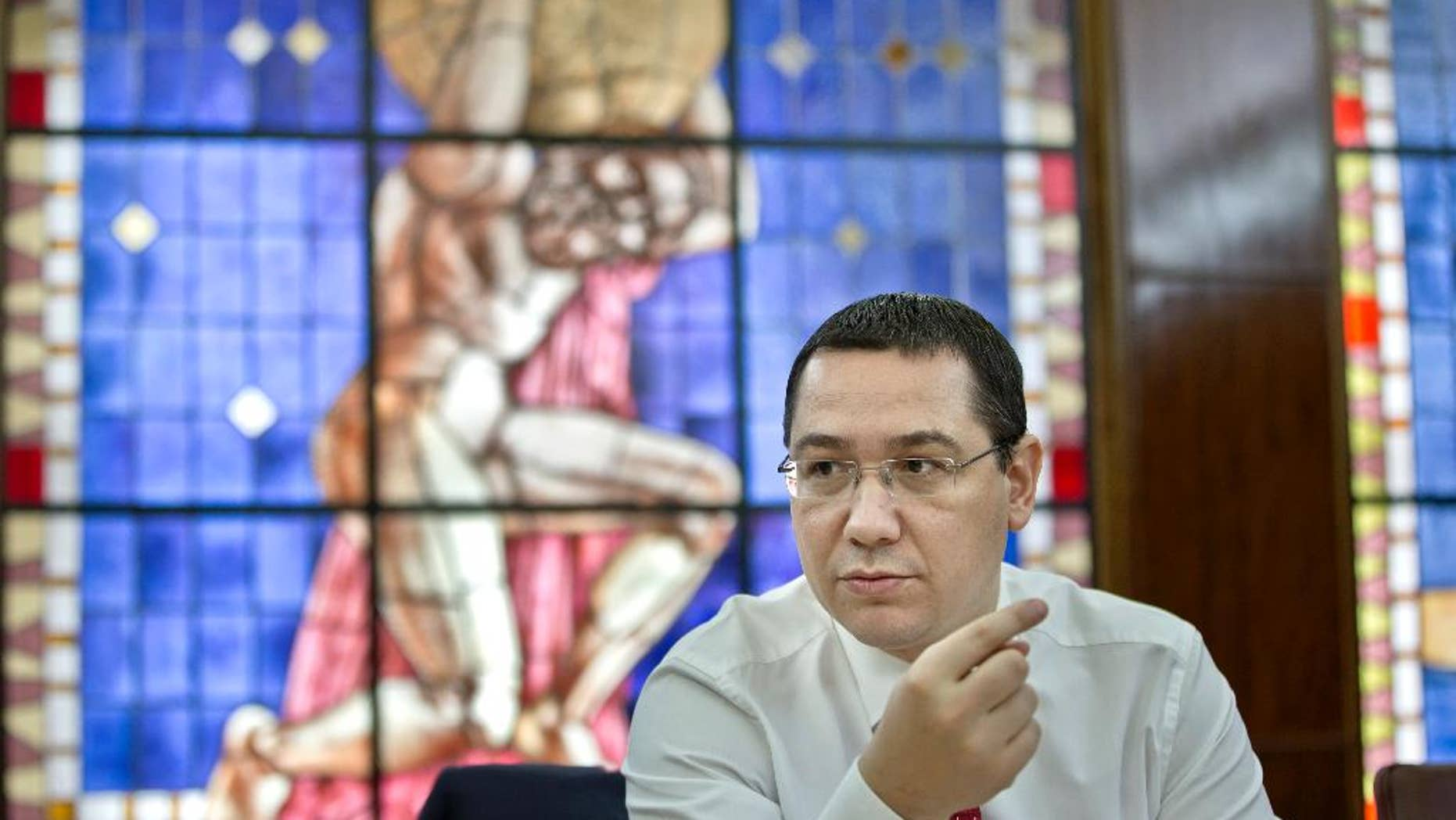 Romanian Prime Minister Victor Ponta gestures during a meeting with the foreign media in Bucharest, Romania, Thursday, May 7, 2015. Romania's prime minister says the European Union has suspended 1 billion euros ($1.13 billion) in funding for Romanian projects over allegations of corruption and irregularities. (AP Photo/Vadim Ghirda)